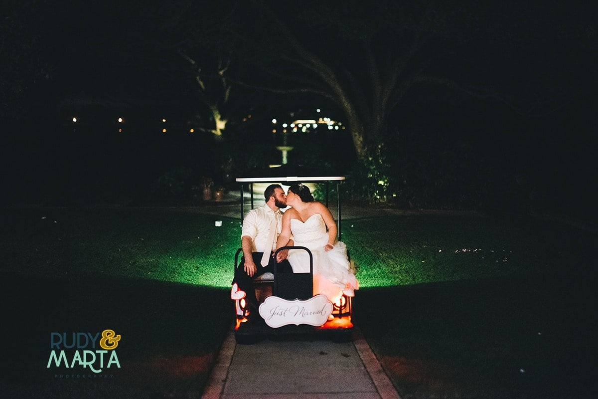 bride and groom kissing on golf cart