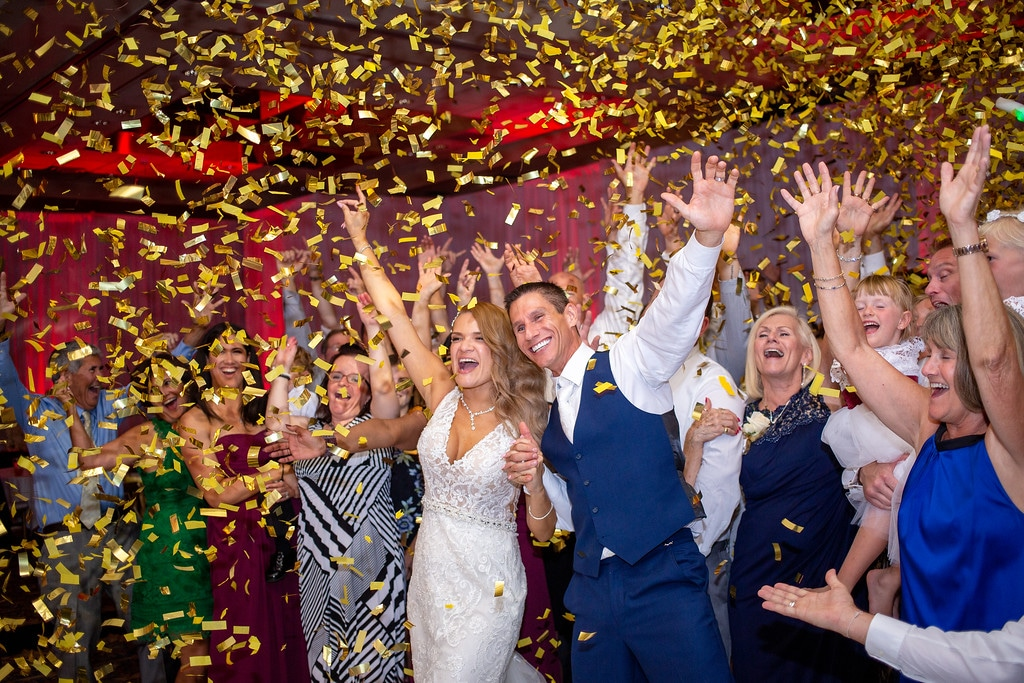 wedding guests cheering under gold confetti shower
