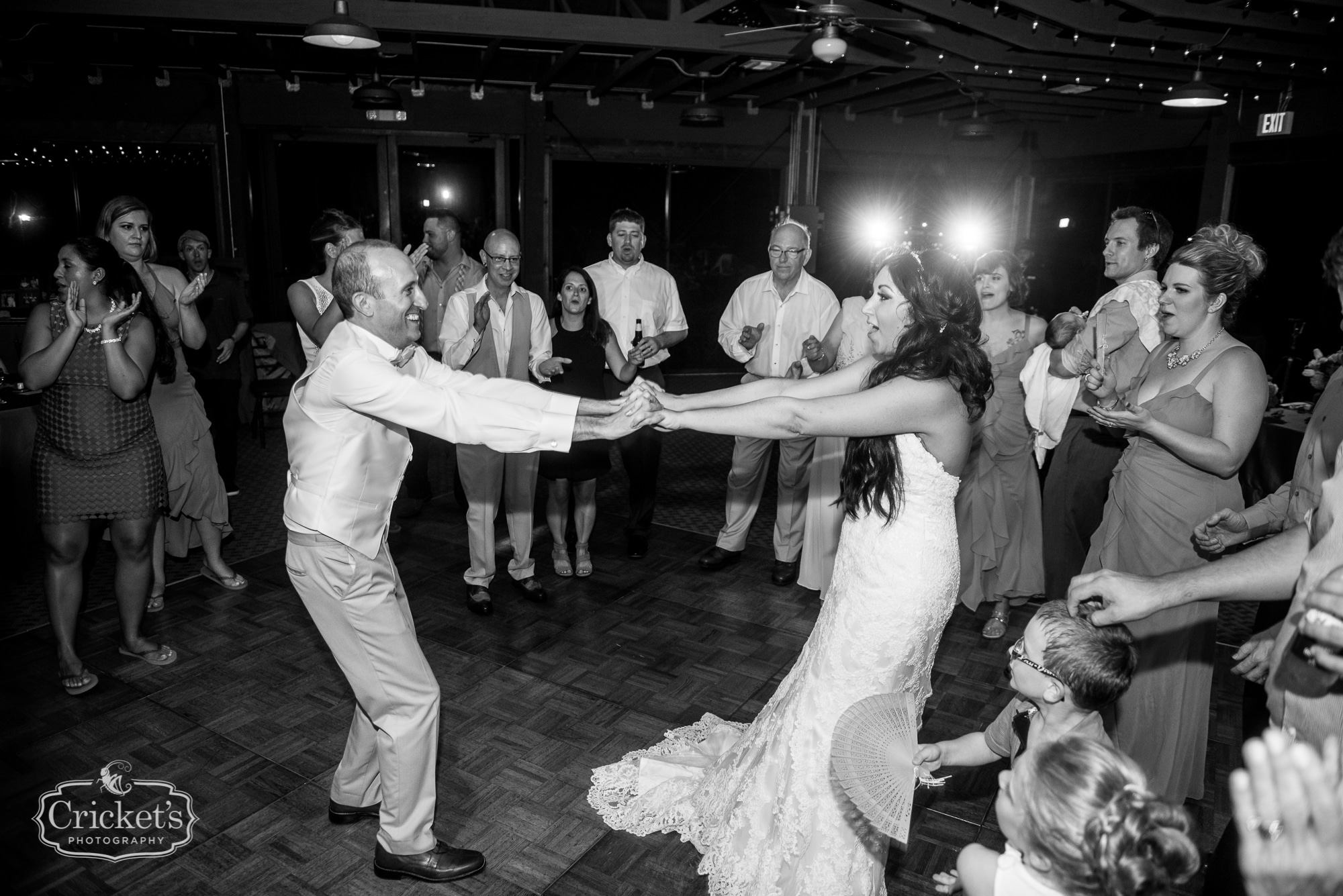 Bride and groom holding outstretched hands on dance floor