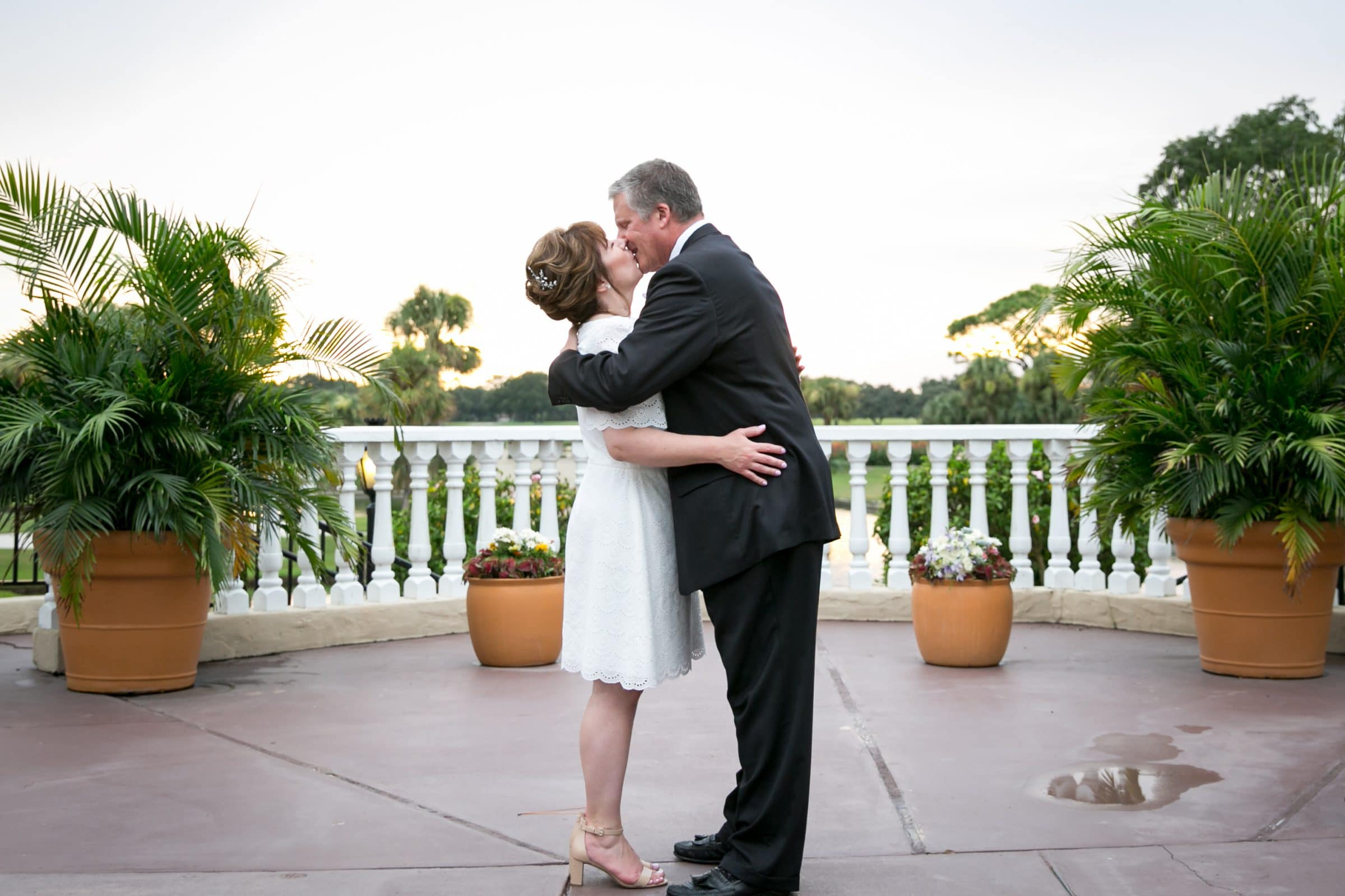 Bride and groom kissing in small courtyard