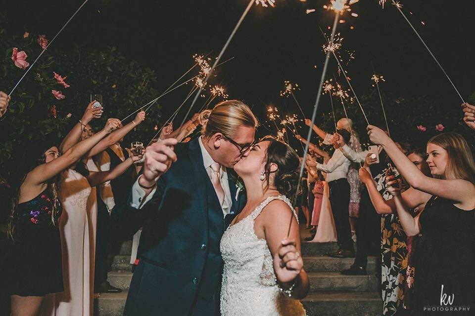 Bride and groom kissing during sparkler sendoff