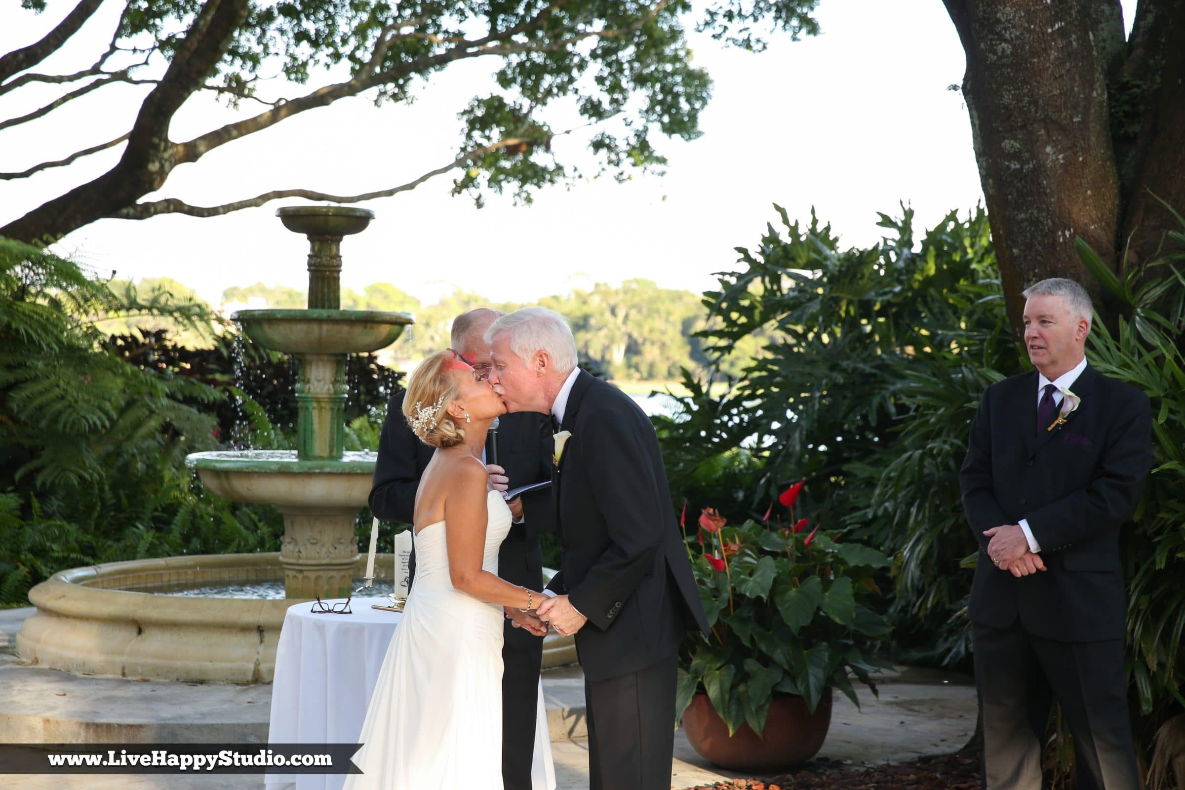 Bride and groom's first kiss under oak tree by rustic fountain