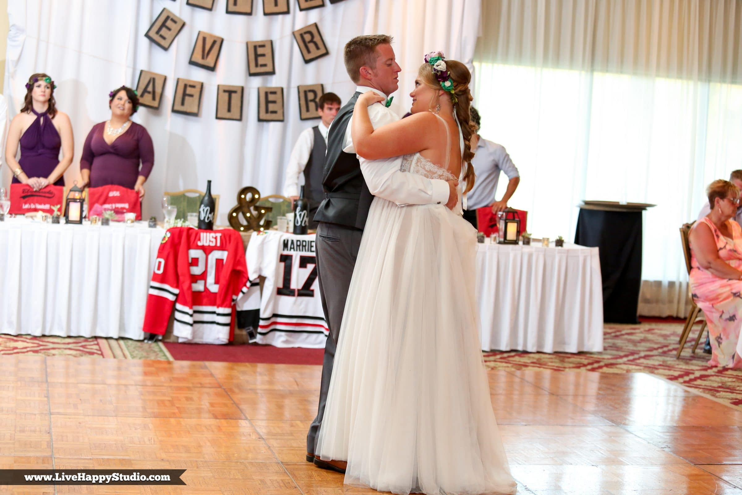 """Bride and groom's first dance in front of sweetheart table with custom """"just married"""" hockey jerseys"""