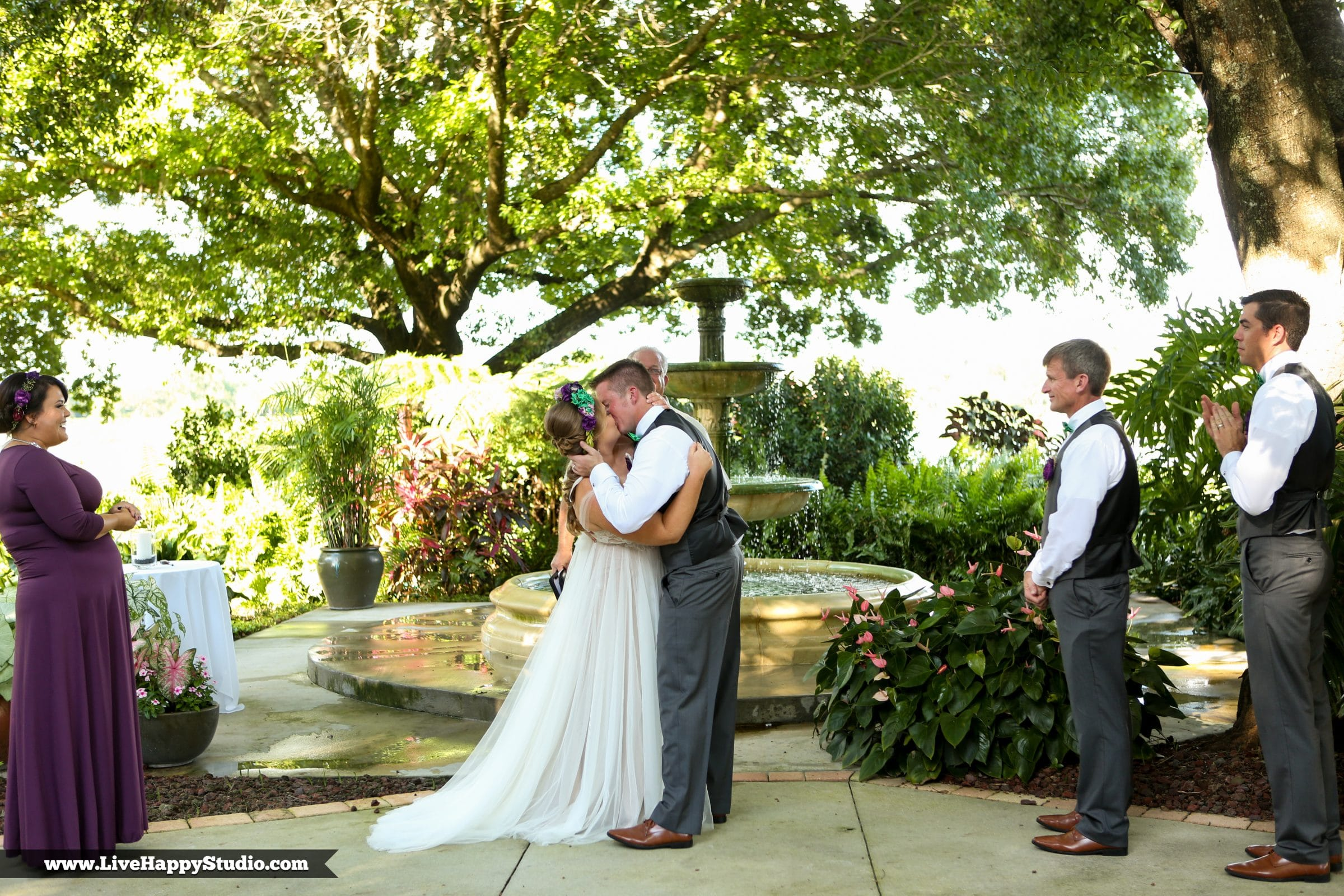 Bride and groom's first kiss in front of rustic fountain in Legends Courtyard