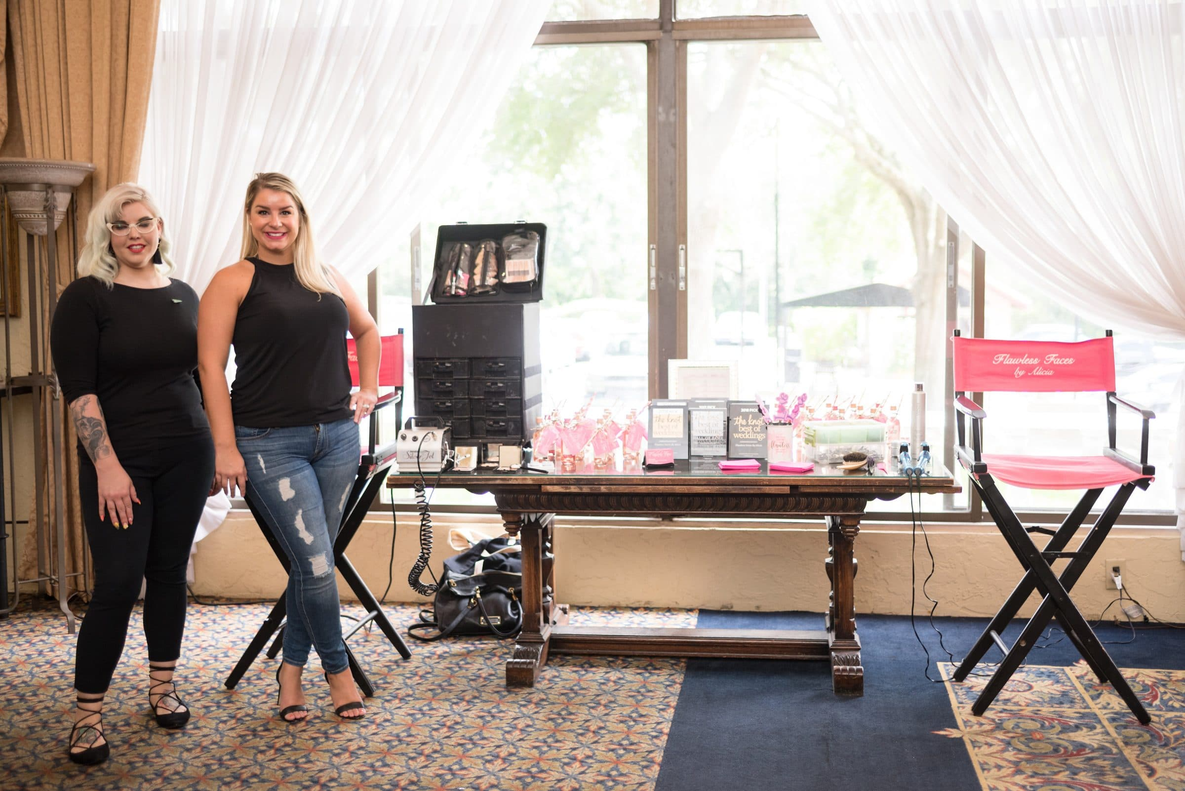 Makeup Artist standing in front of table with makeup and bottles of champagne