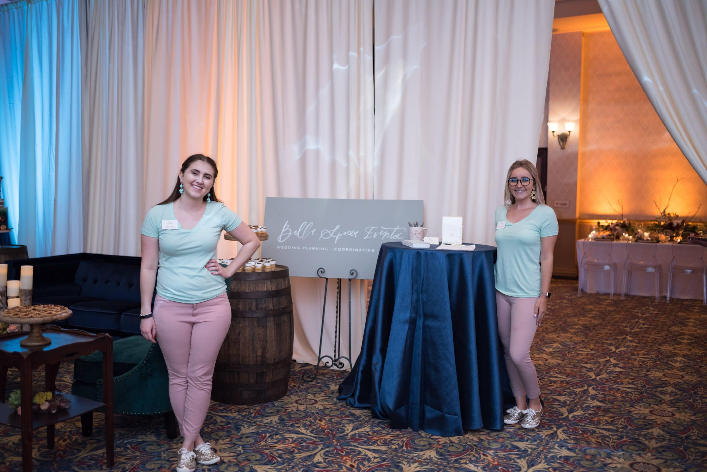 Two girls in pink pants and blue shirts with sign reading Bella Sposa