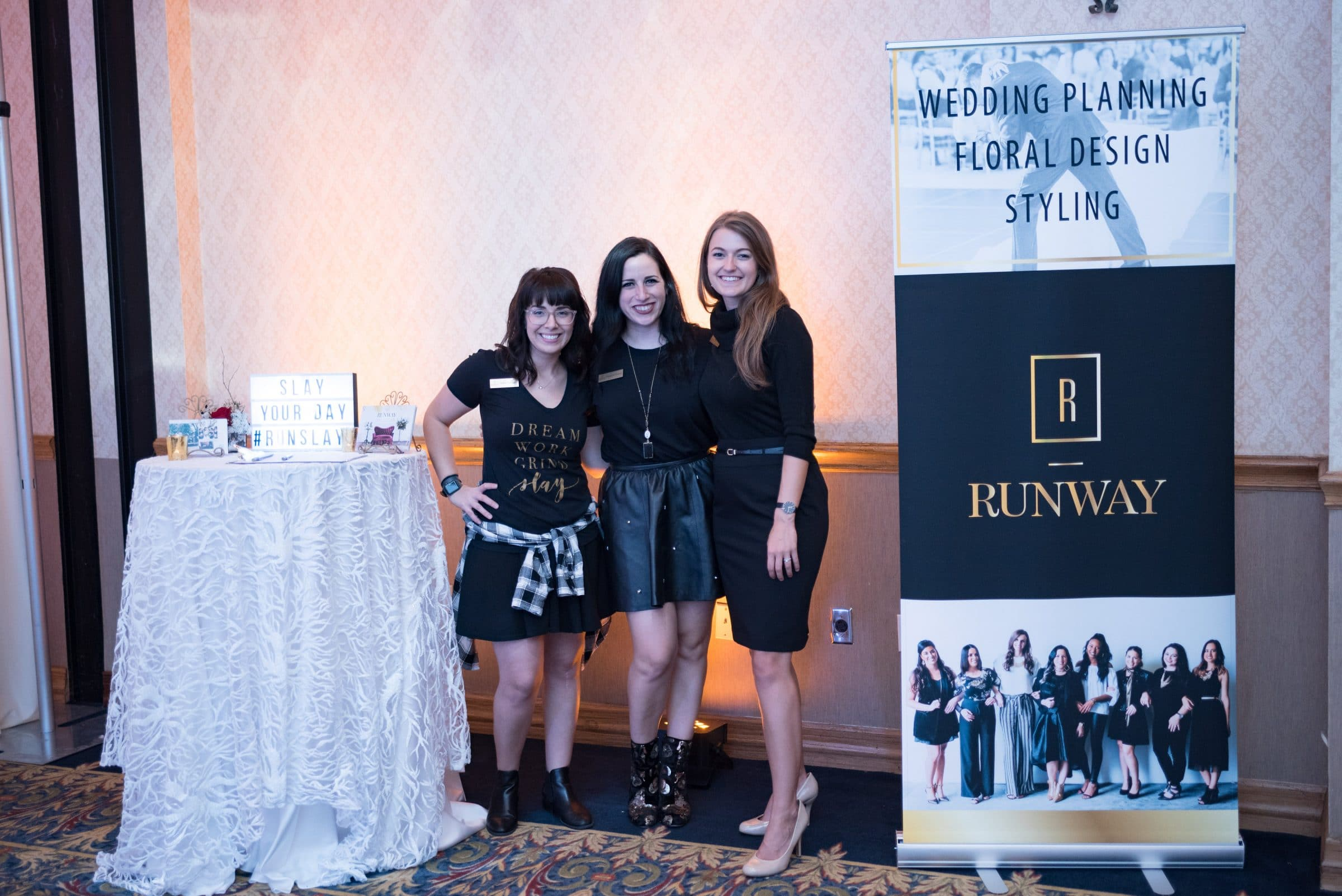 Three Wedding Planners next to Runway Events Sign
