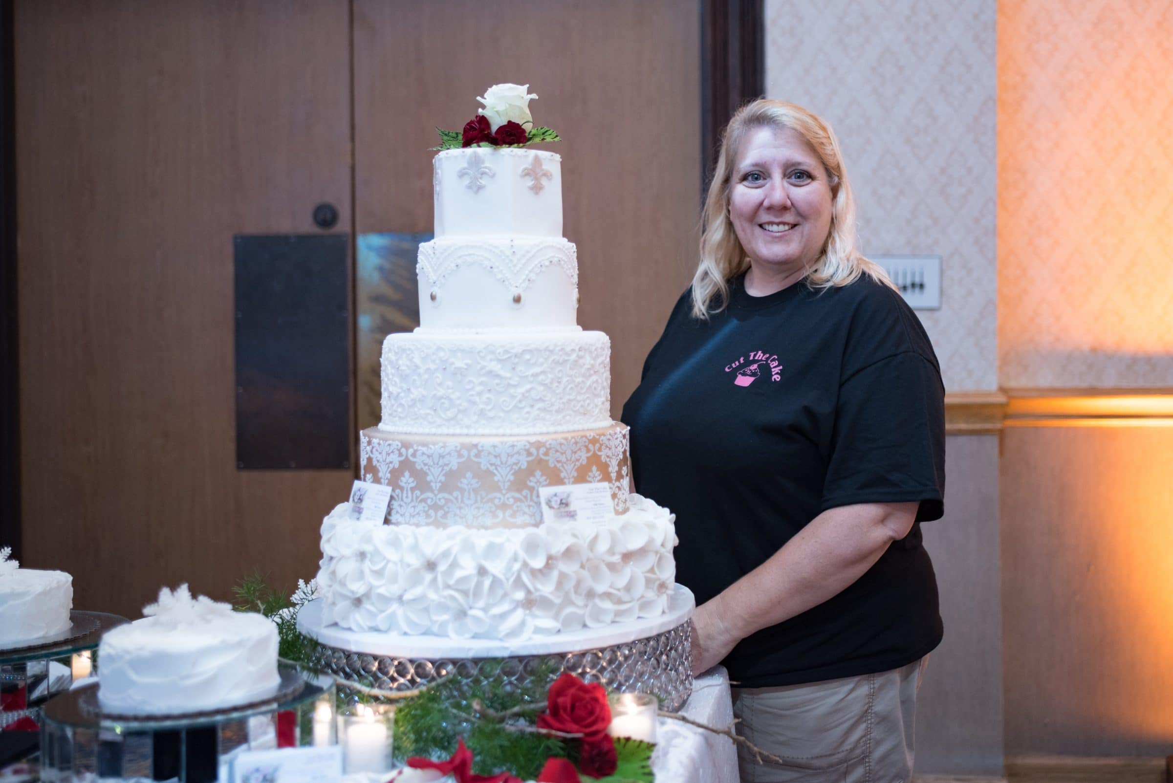 Woman standing next to five tier wedding cake