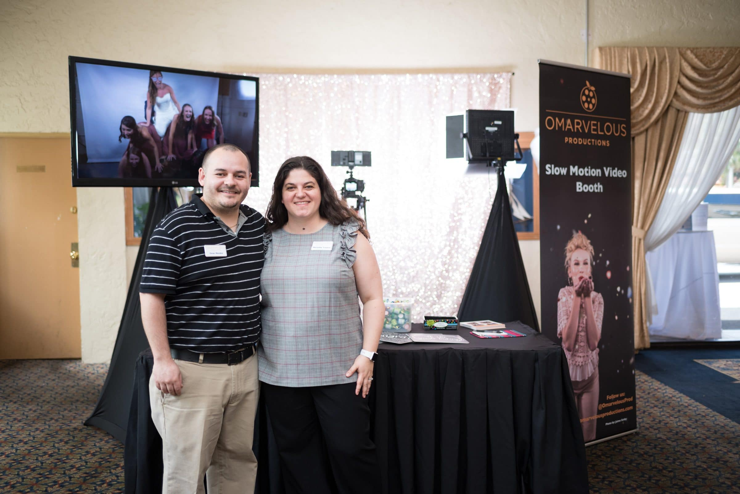 Man and Women standing in front of black table with slow motion video booth