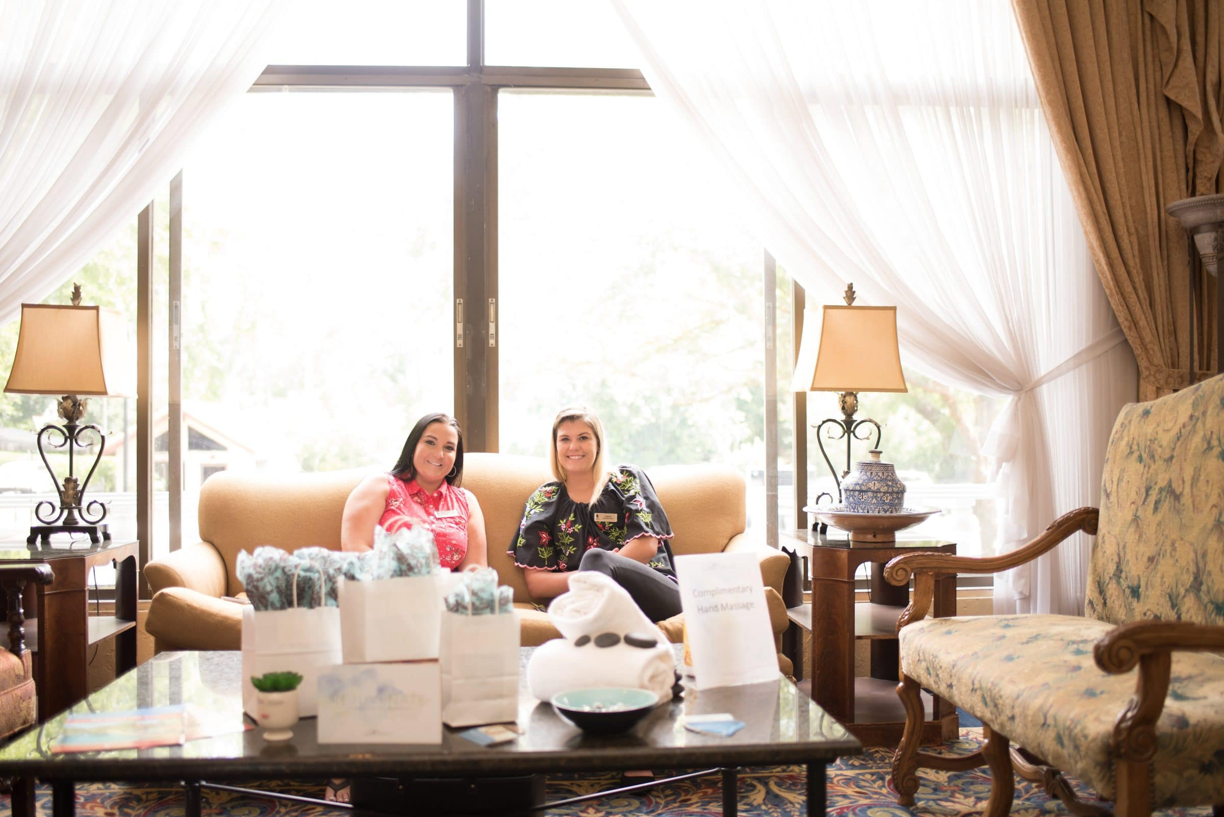 Two women sitting on a couch featuring spa services