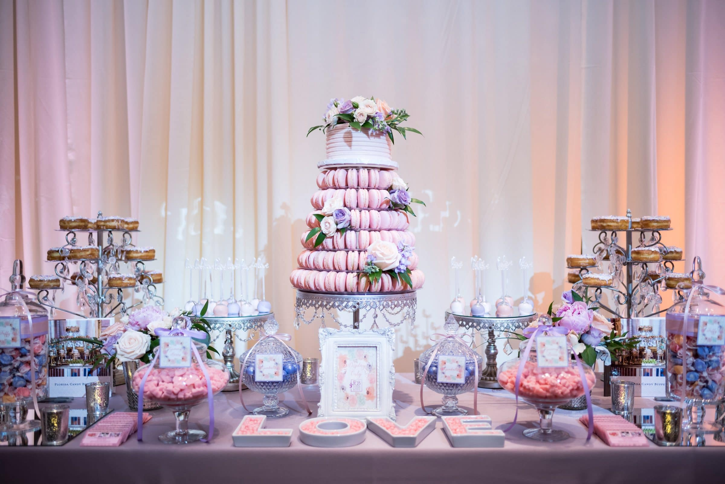 Tower of Pink Macaroons on a Table of Assorted Pink and Purple Desserts