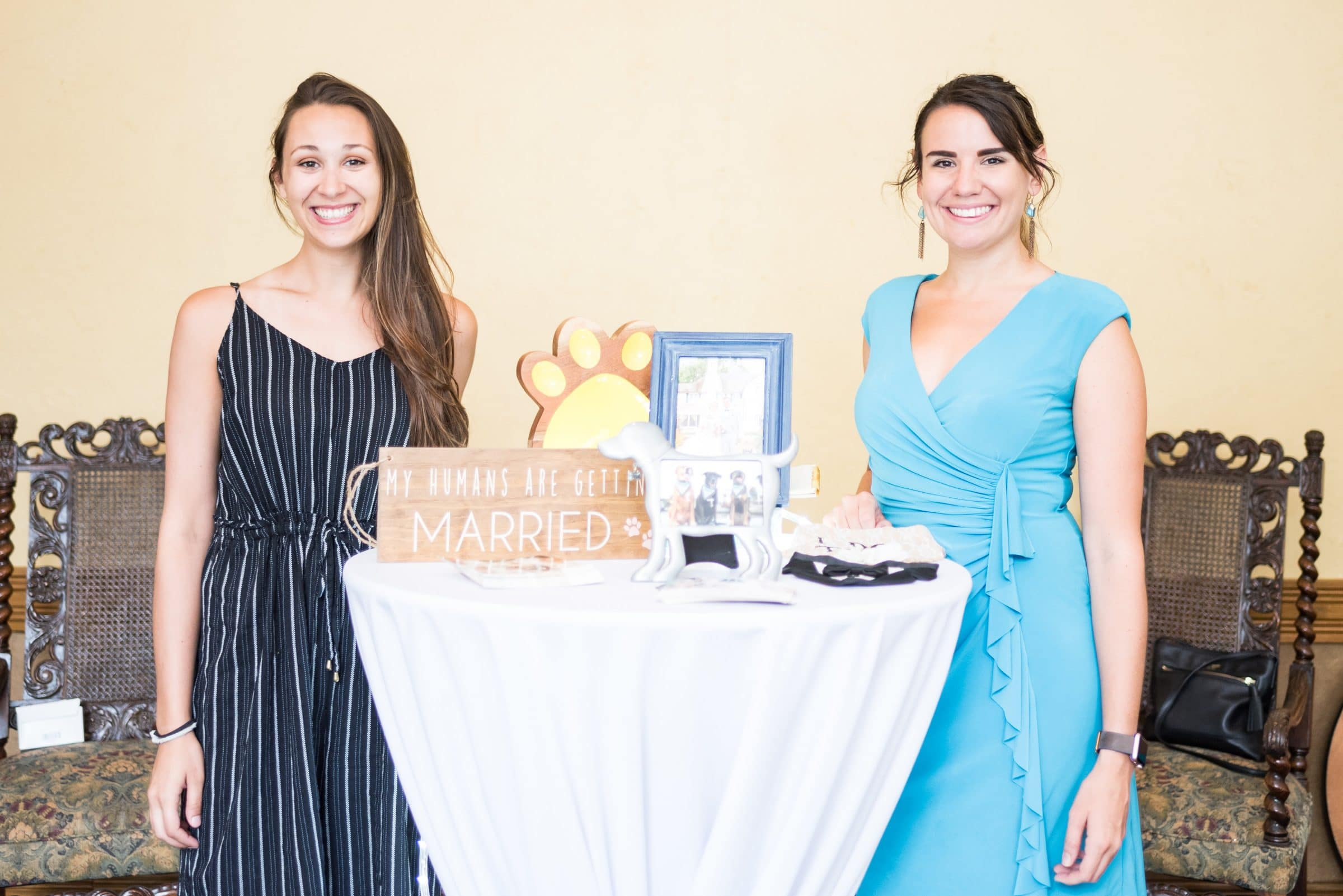 Two Girls standing at a table in black and blue dresses with dog signs
