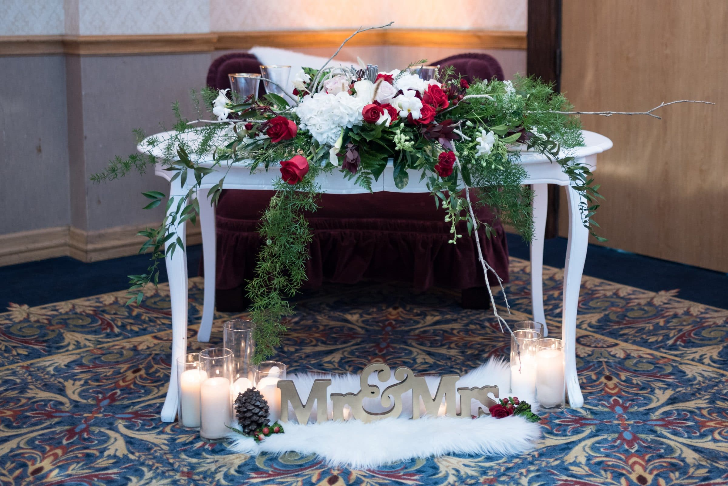 White table with white lighting draped in greenery and red roses