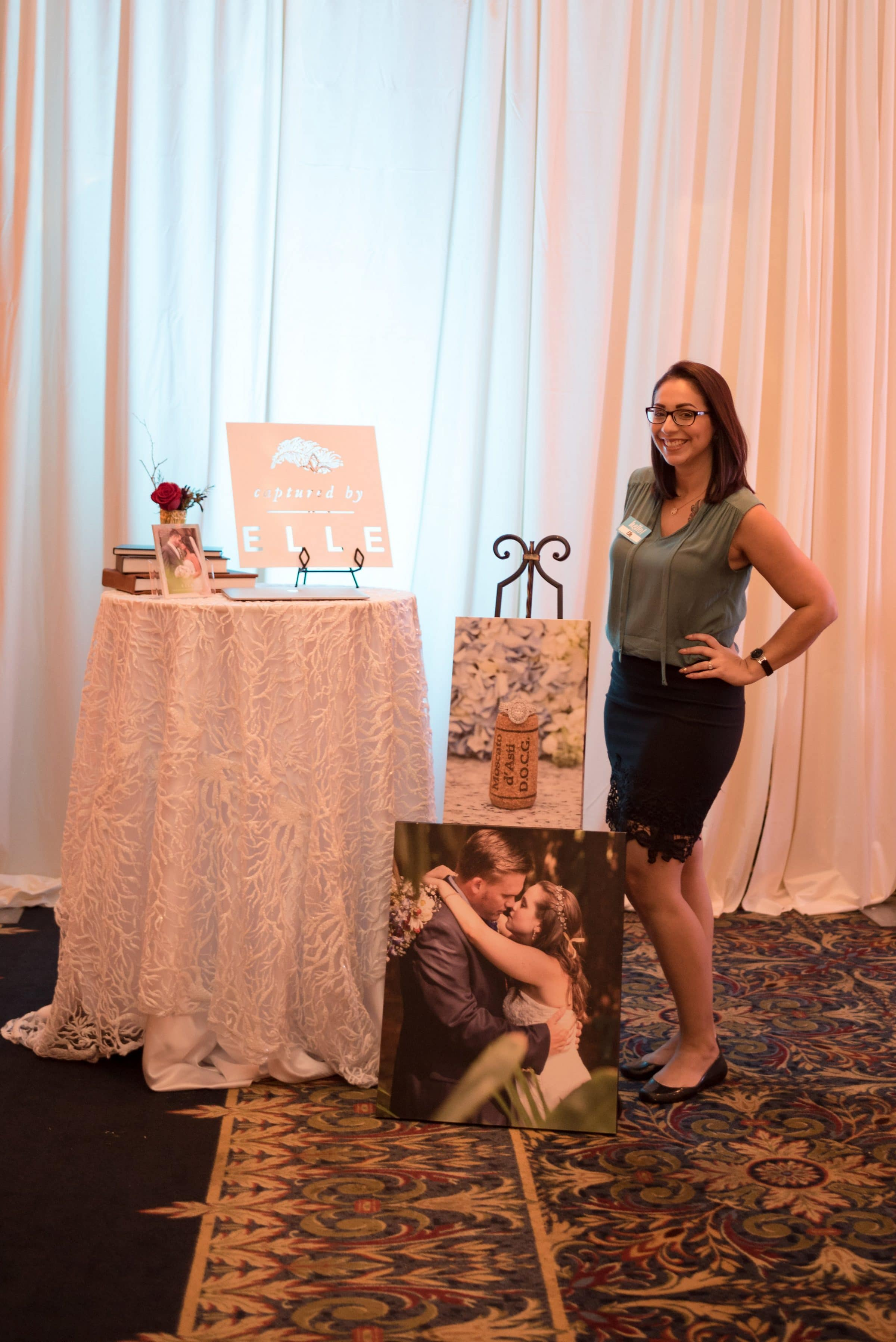 Woman standing next to table and photo easel