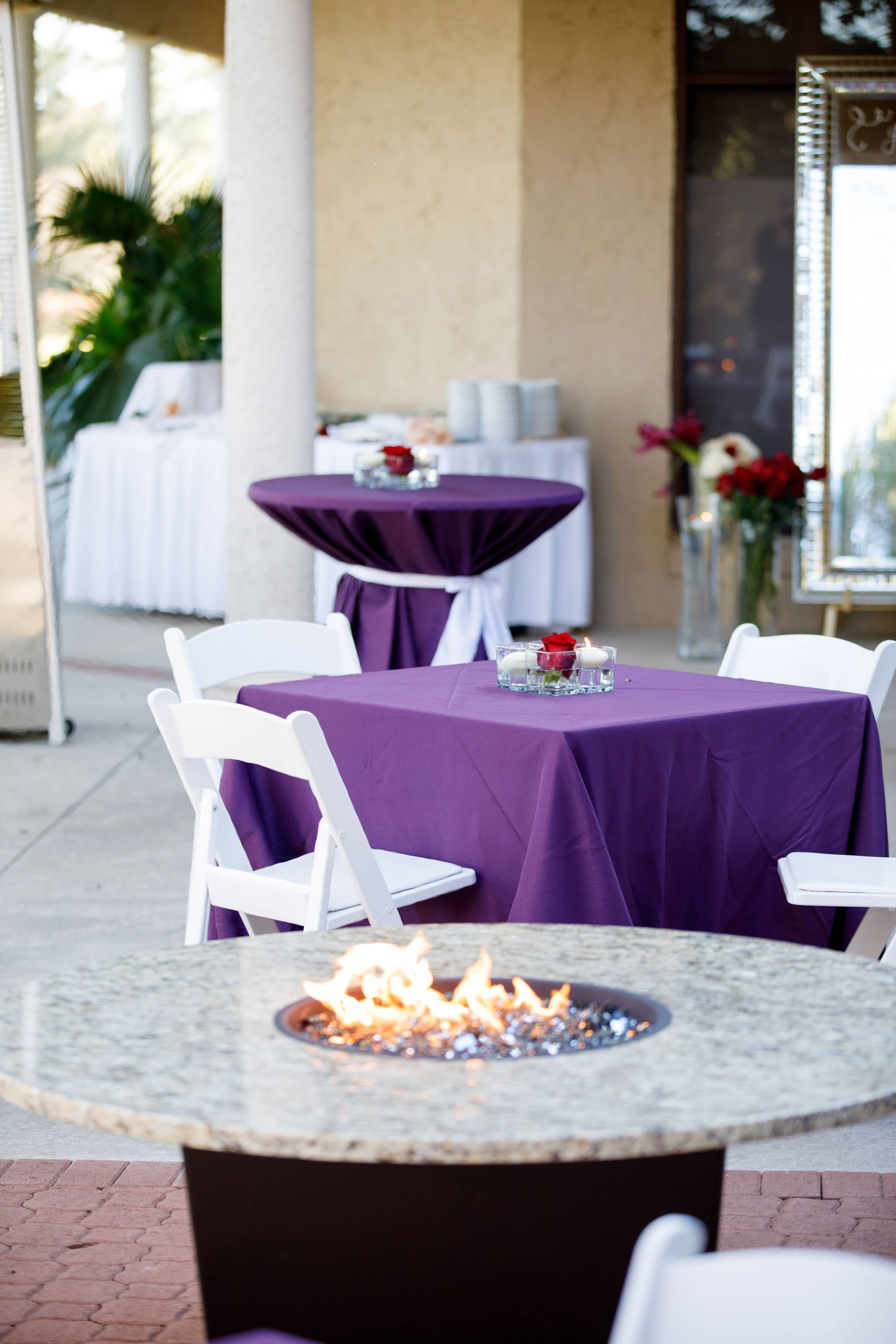 Terrace with white chairs and purple draped tables with fire pit wedding venue questions to ask