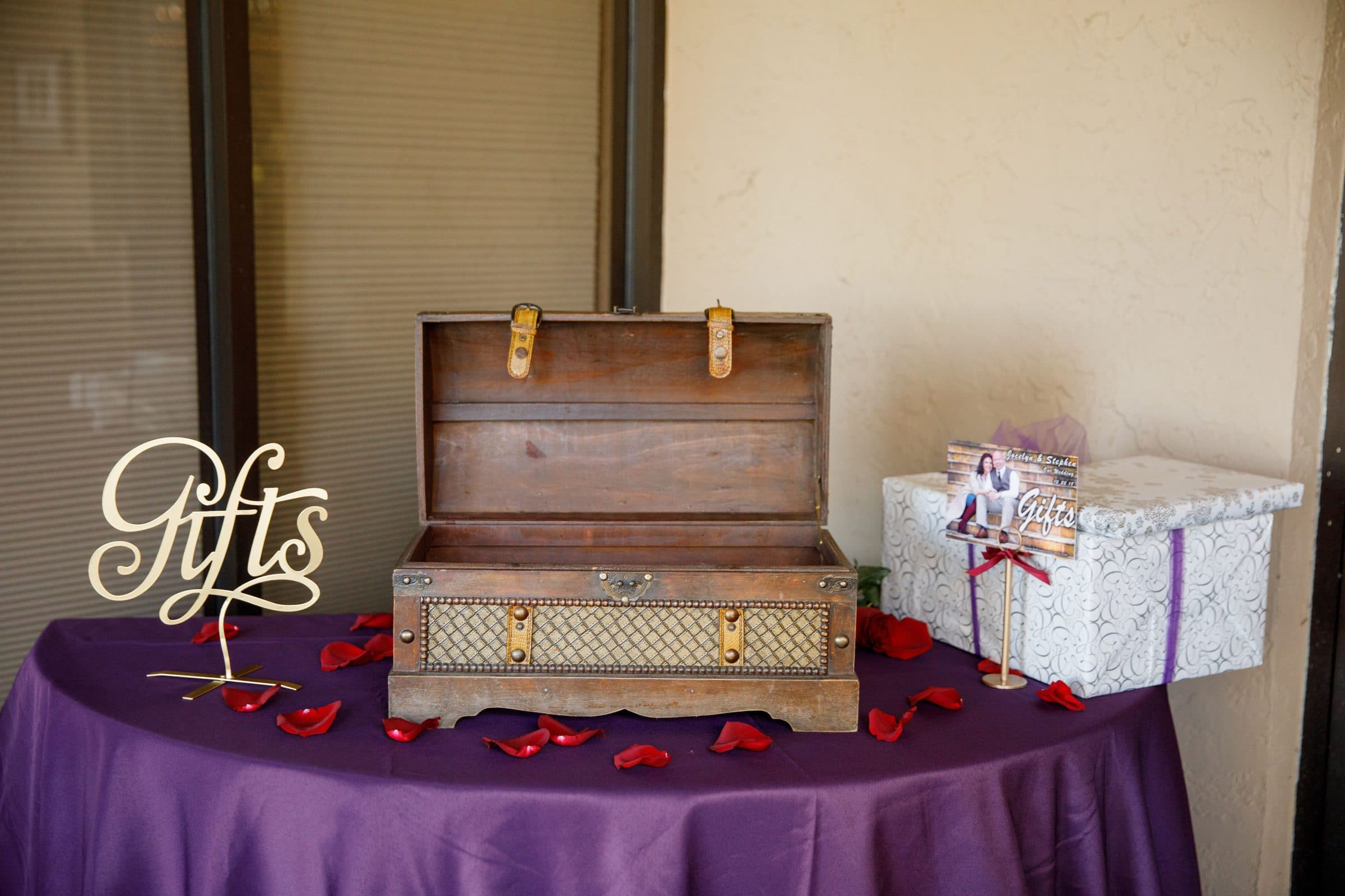 Table with purple linen and red rose petals with gift box