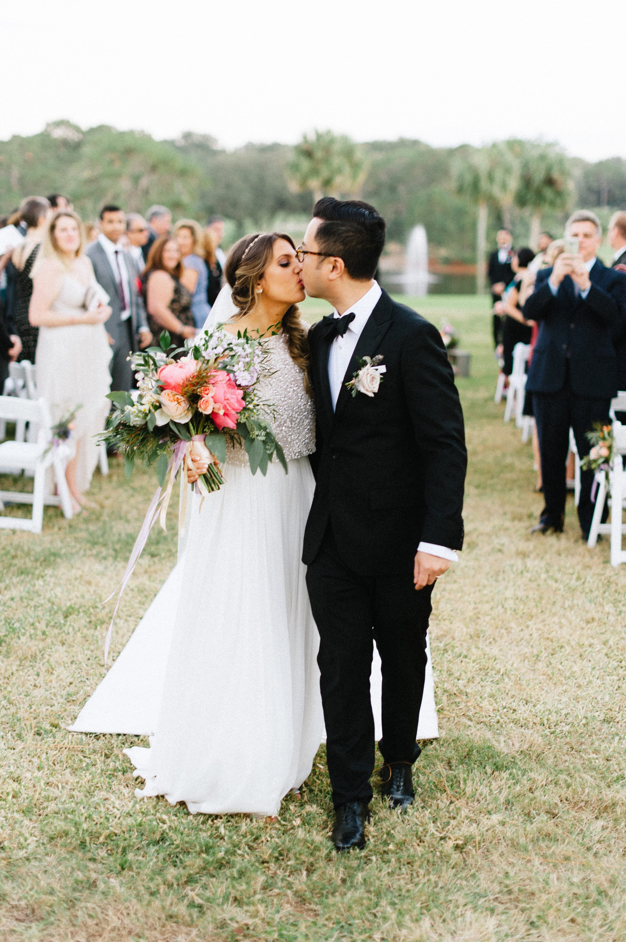 Bride and Groom Kissing while Holding Show Stopping Wedding Bouquet