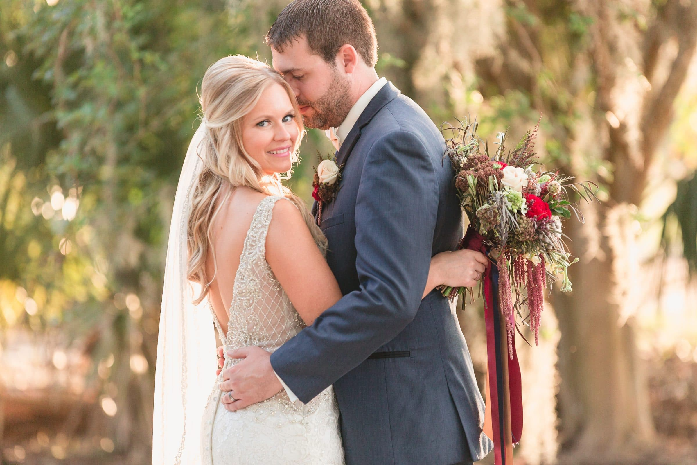 Bride and Groom in Trees holding Harvest Hues Wedding Bouquet
