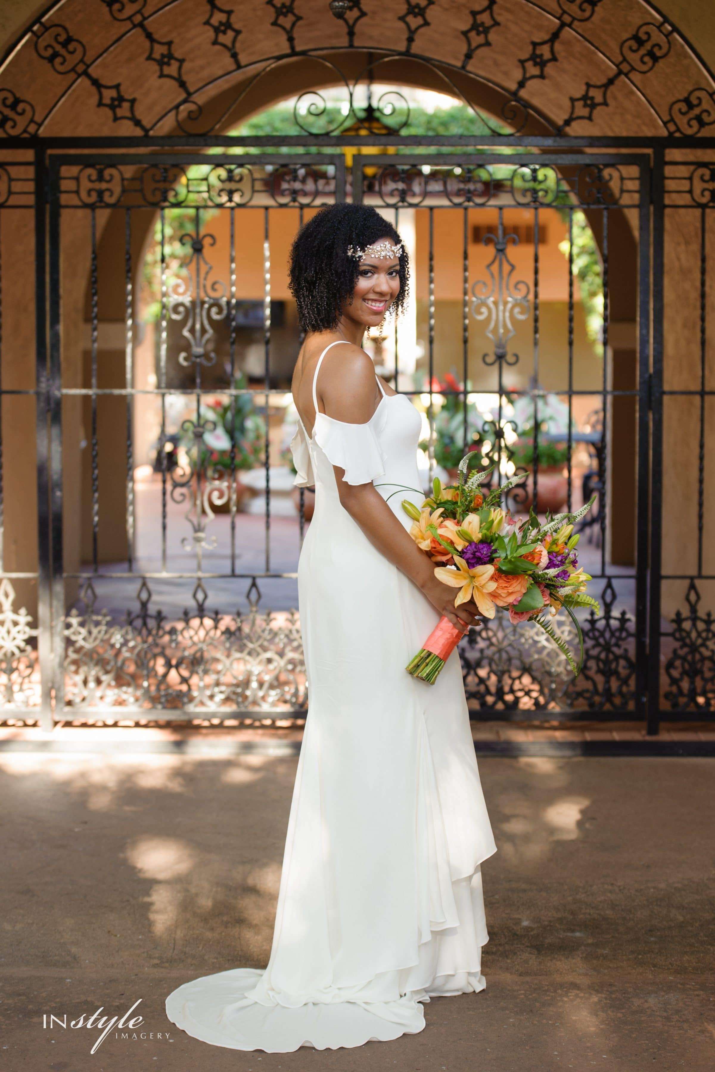 Bride Holding Palm Springs Inspired Wedding Bouquet in front of Mission Inn Iron Gate