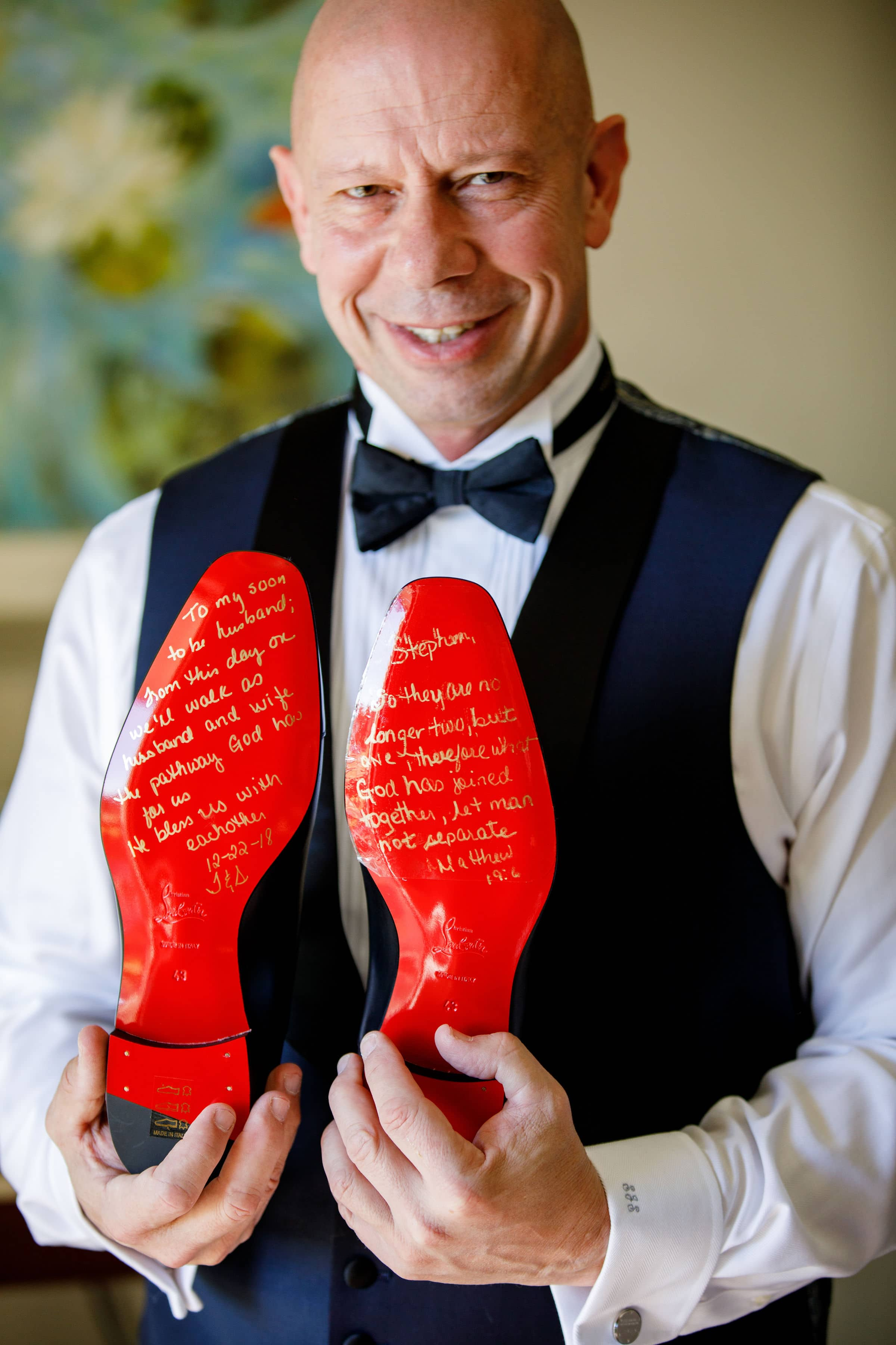 Groom holding red shoes with love letter on sole