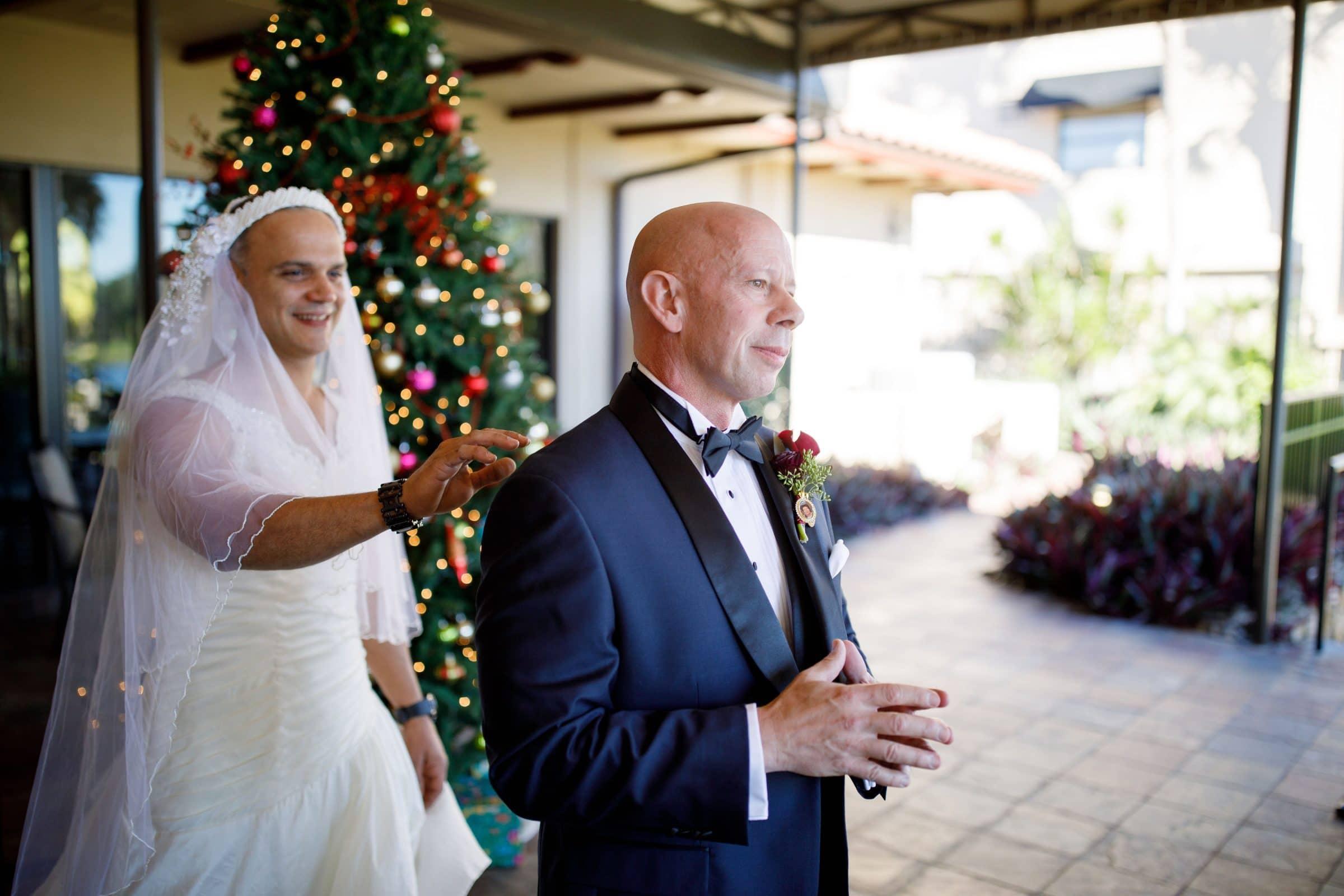 Man in wedding dress touching groom's shoulder