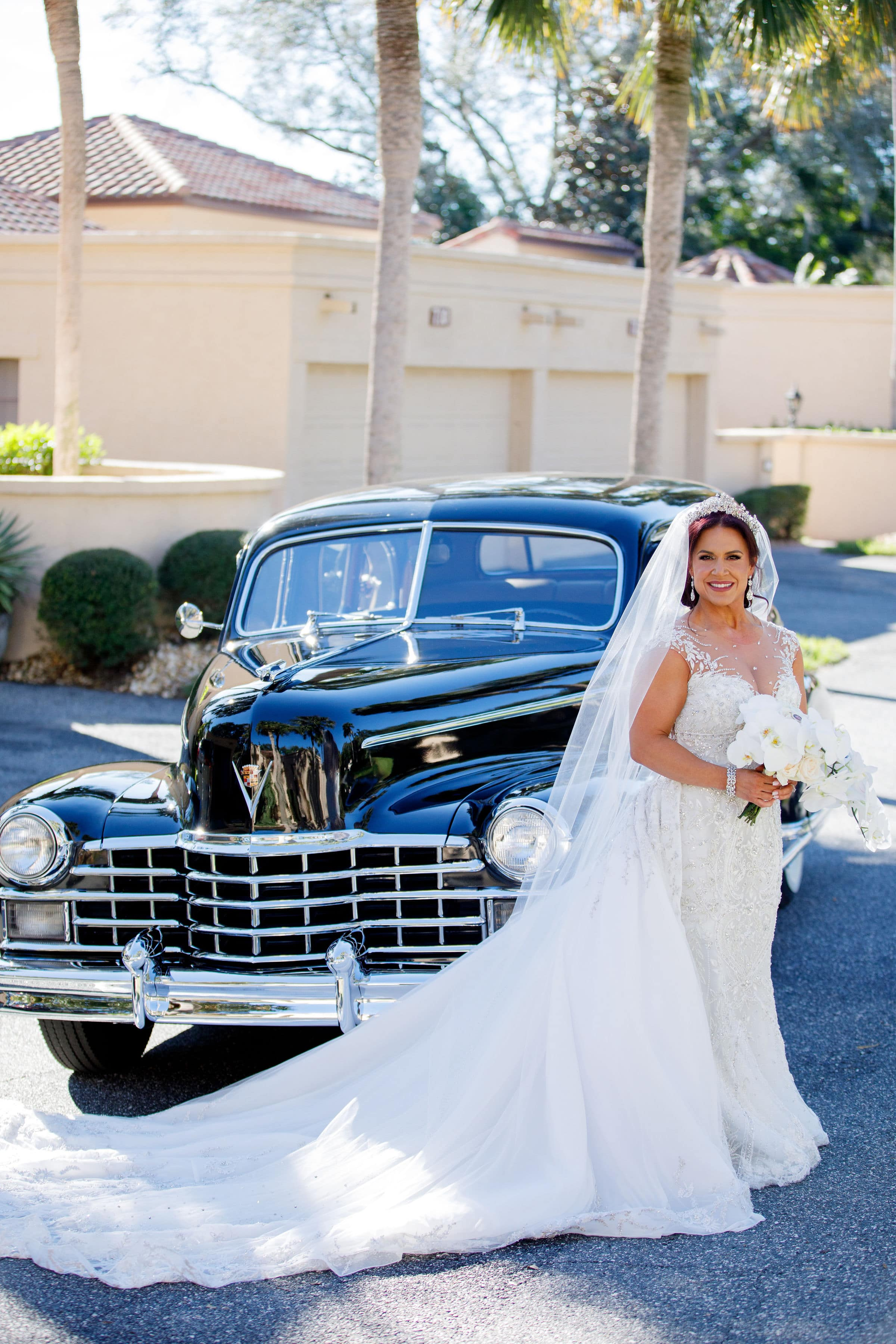 Bride in front of a black Cadillac limousine