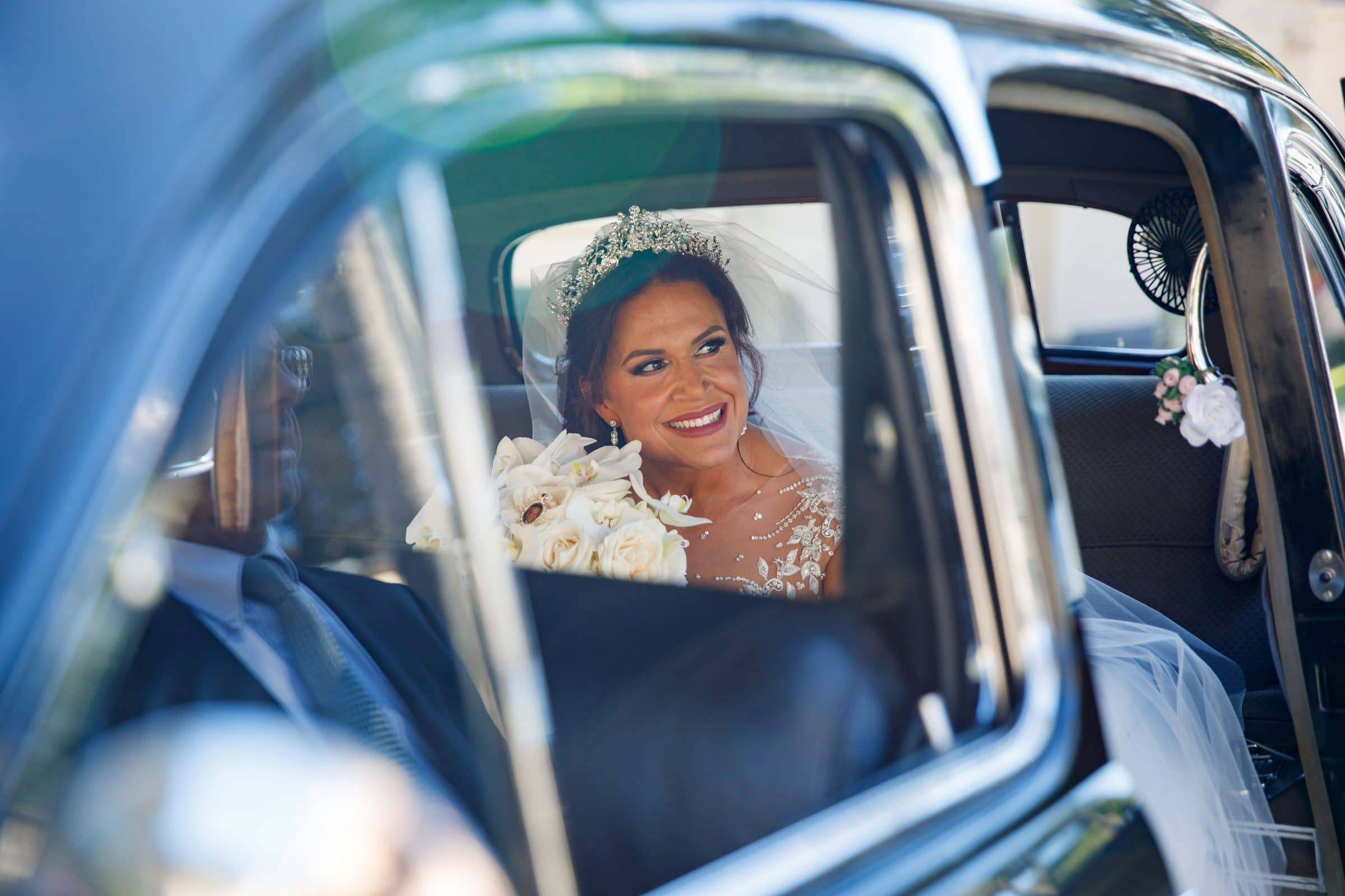 Bride looking through the window of an antique Cadillac Limo