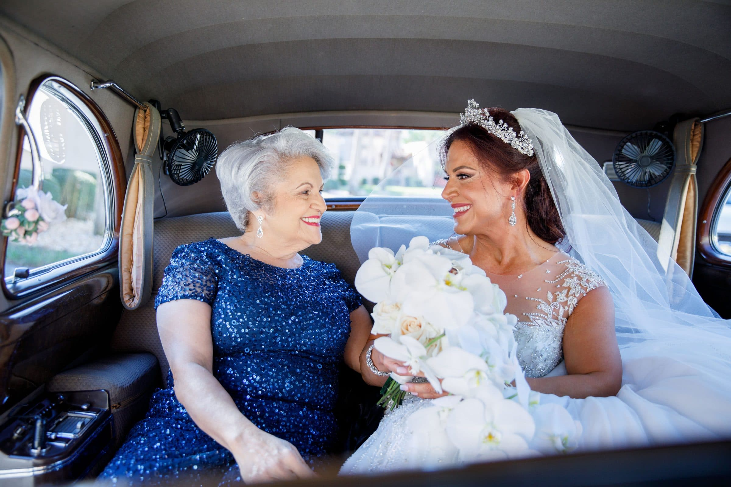 Mother in blue dress sitting with bride in limosuine