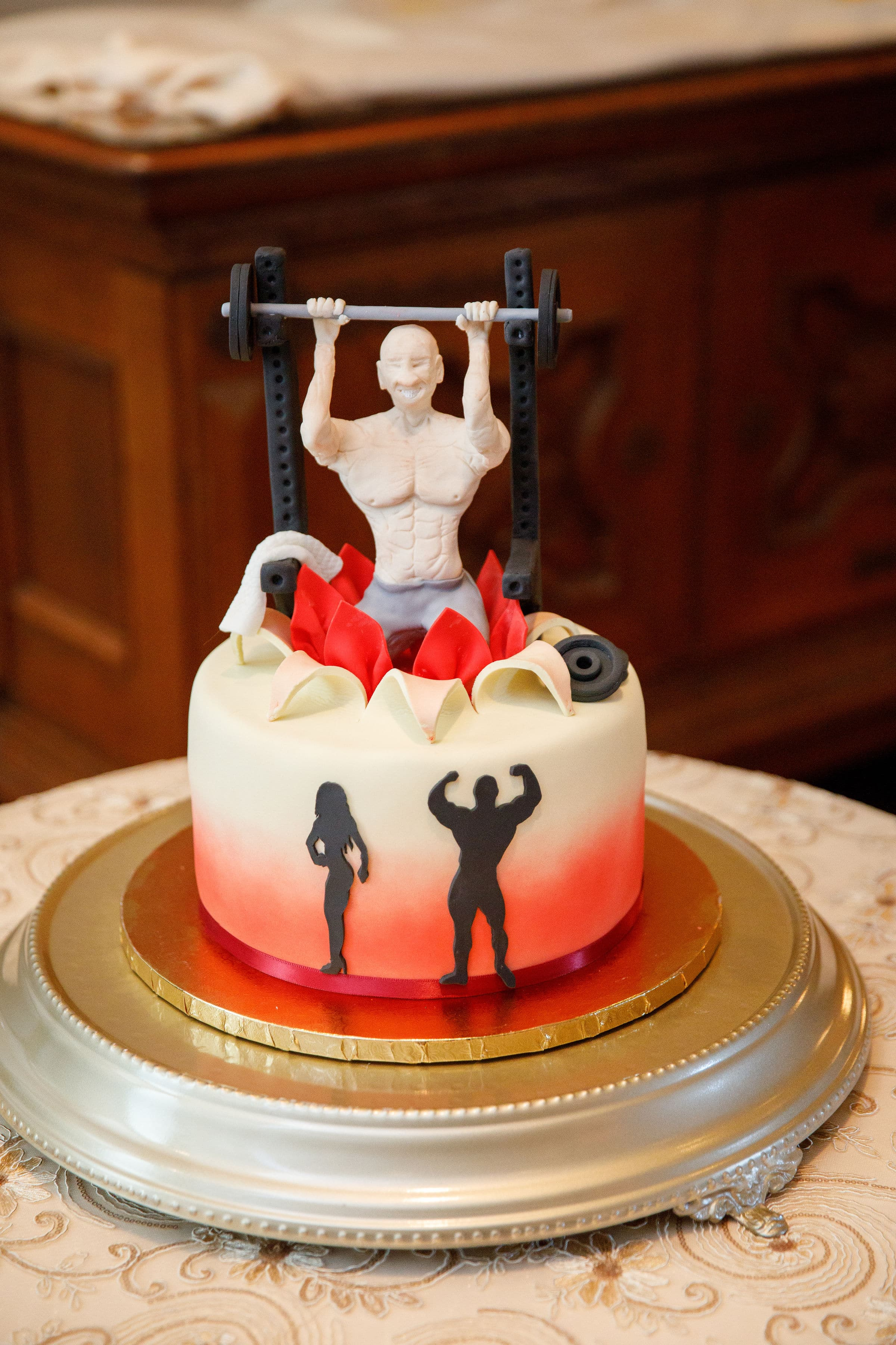 Cake with weight lifting man popping out of cake