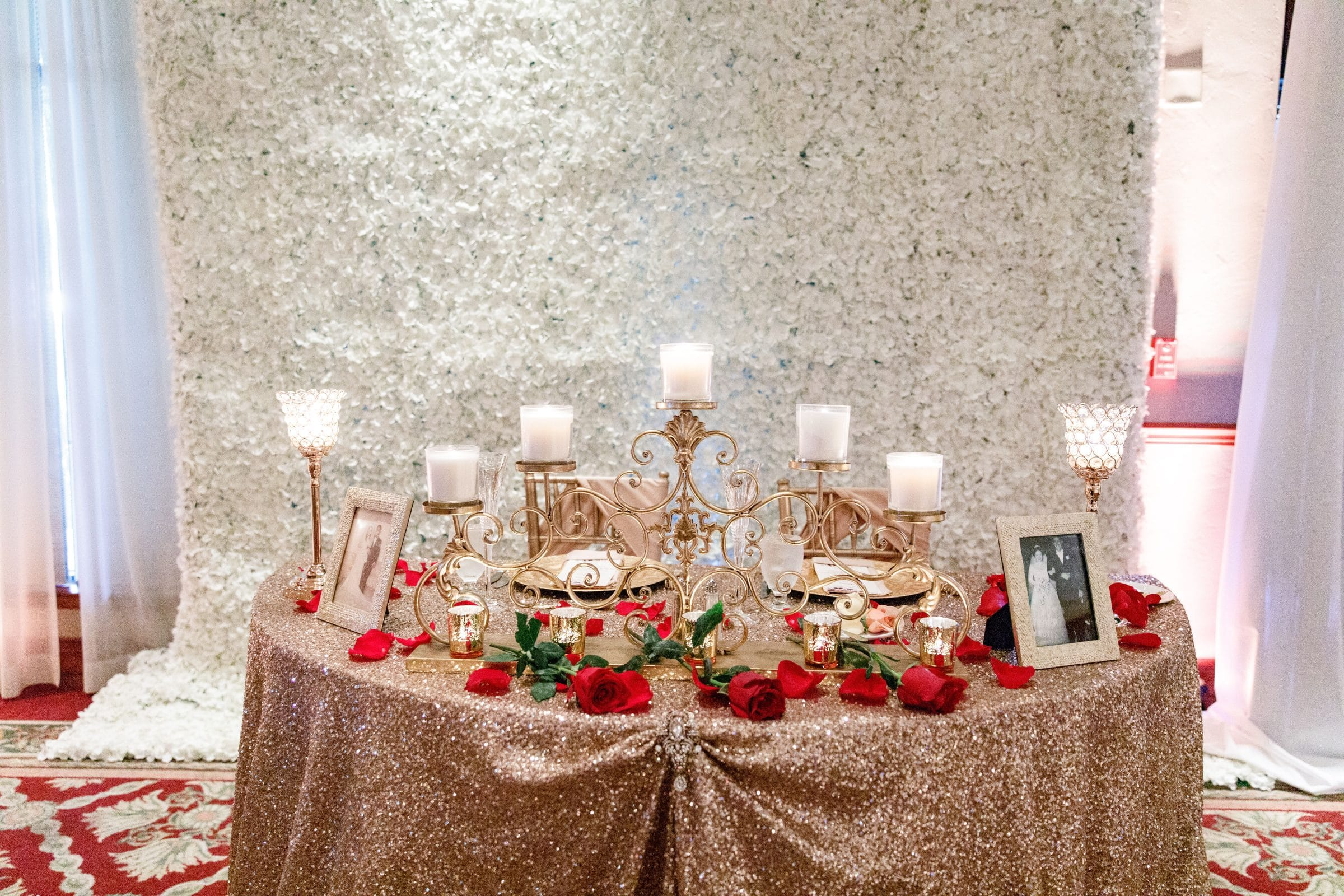 Gold Table with Candles in front of flower wall