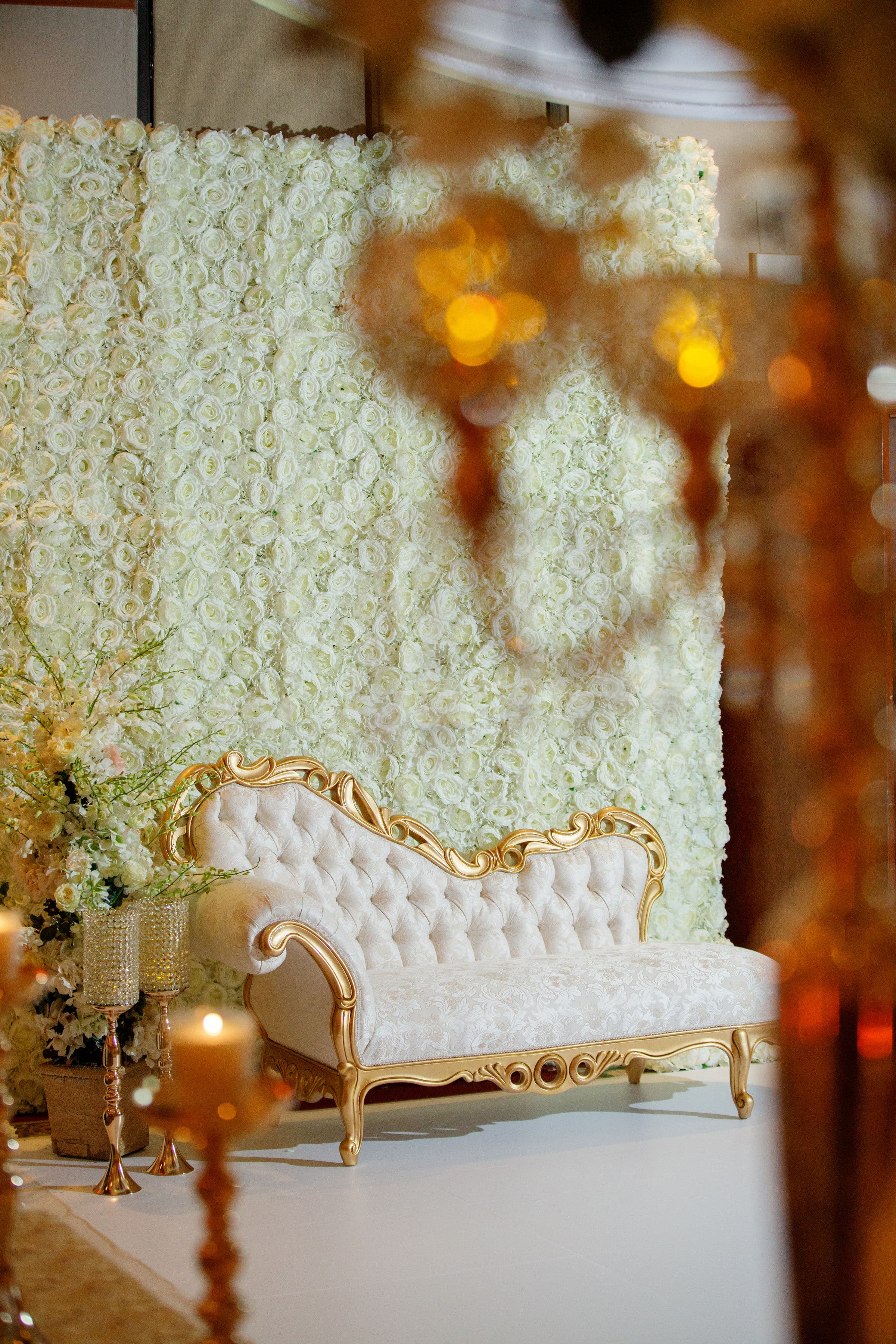 White and Gold Chaise Loung in front of flower wall
