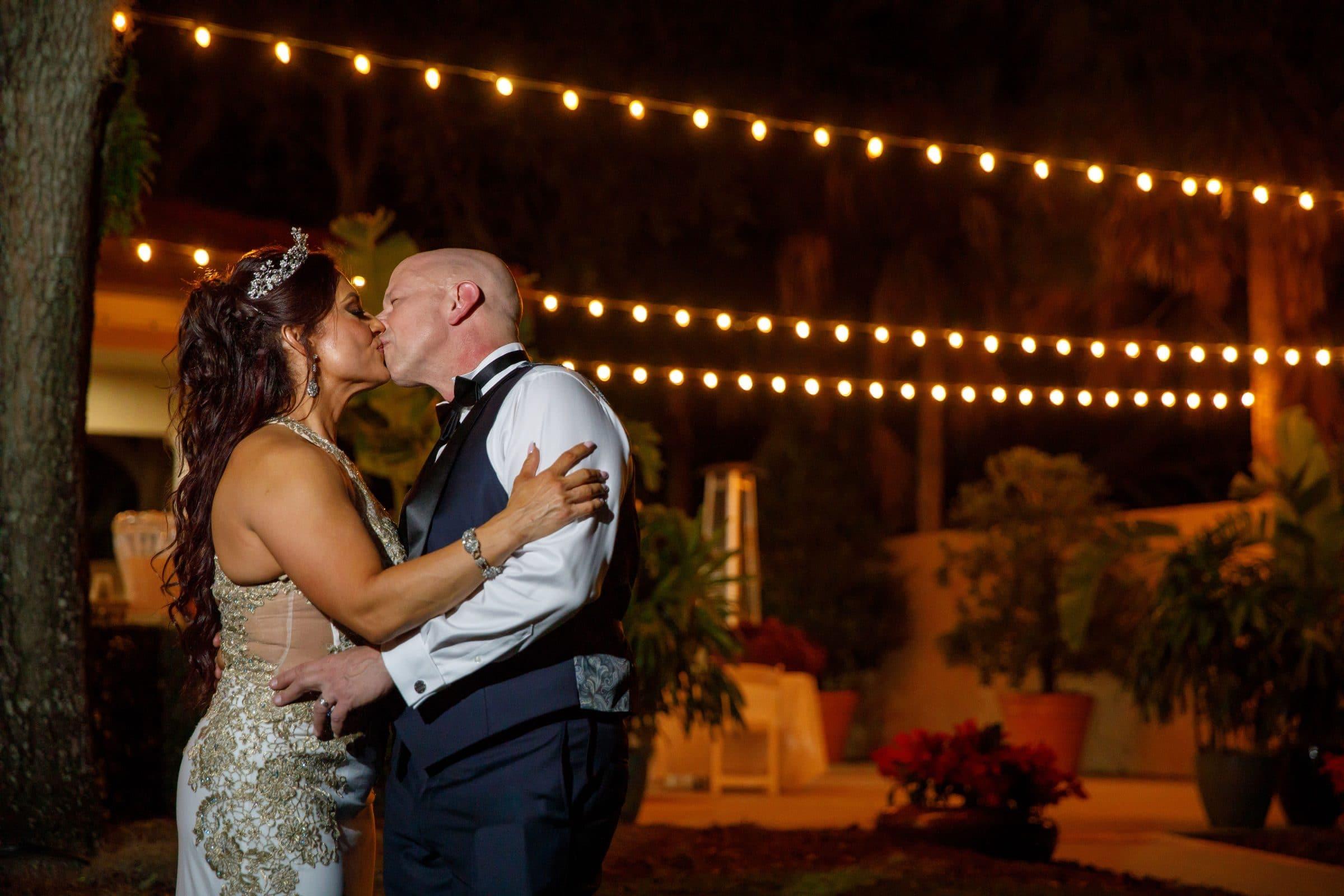 Bride and Groom Kissing Under Market Lights
