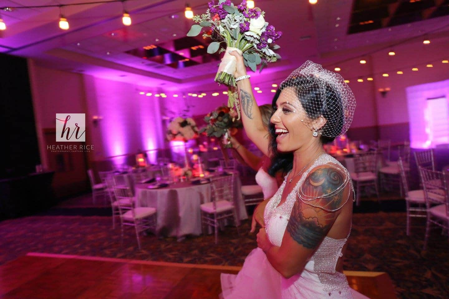 Bride tossing her wedding bouquet in the ballroom