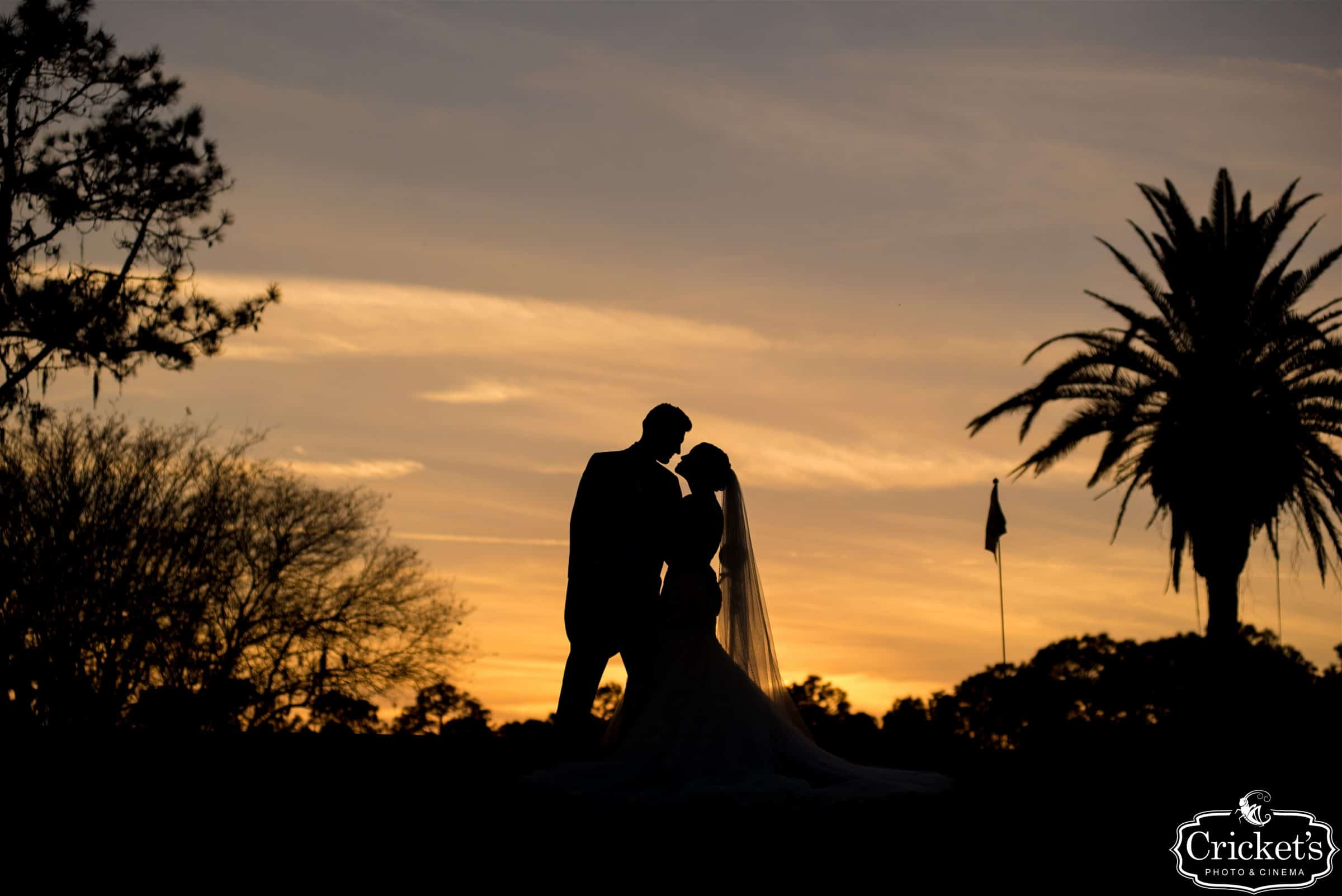 newlyweds on golf course with dramatic sunset