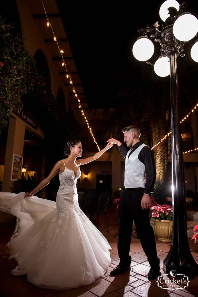 bride and groom dancing under market lights with christmas wedding poinsettia