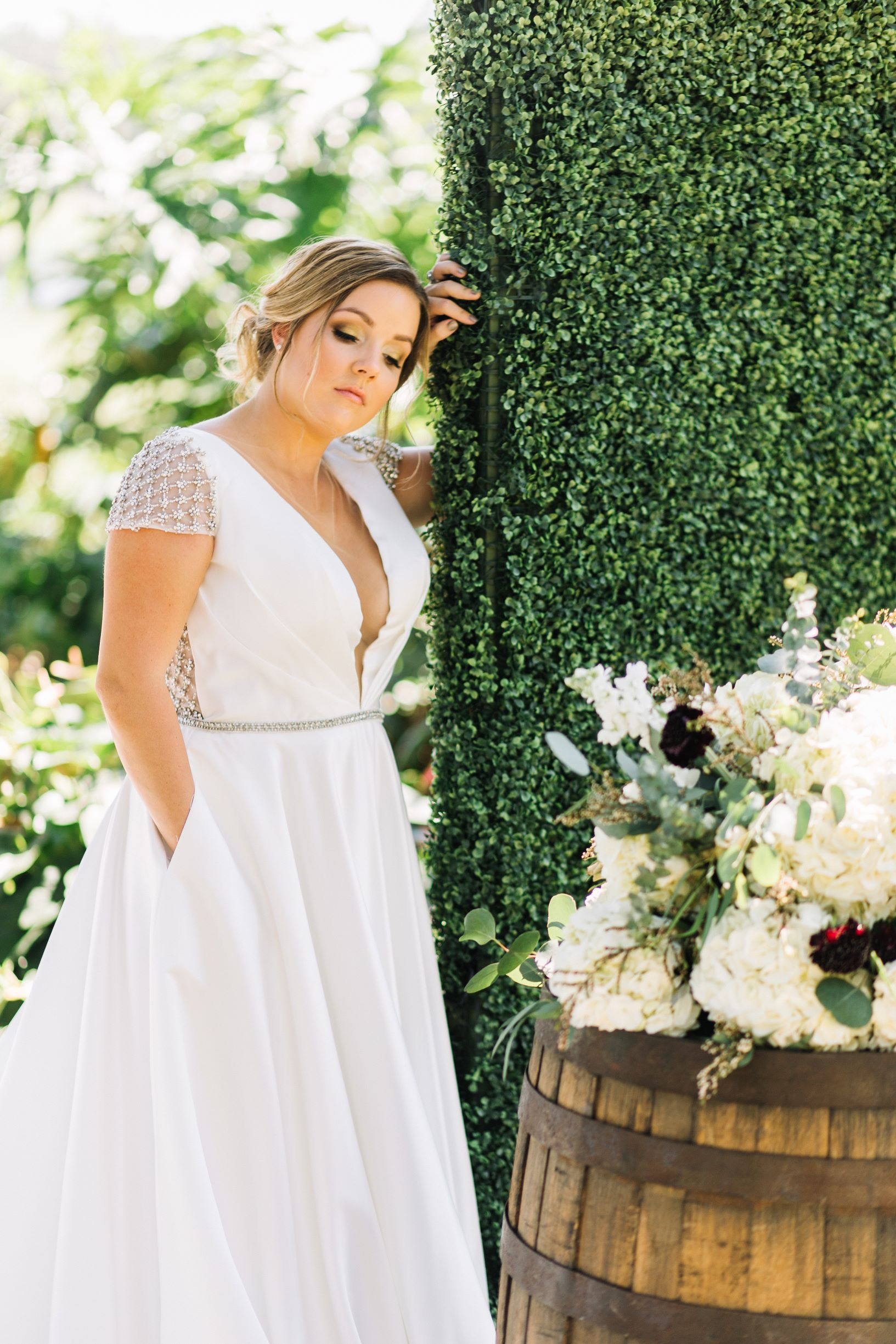 Bride standing in wedding dress with hedge wall and oak barrell