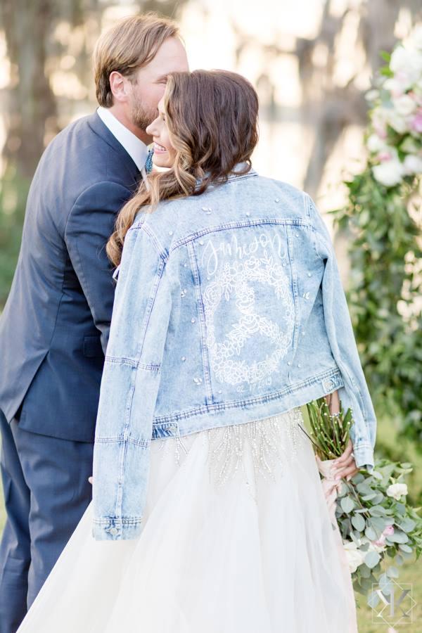 Bride wearing denim jacket over her dress