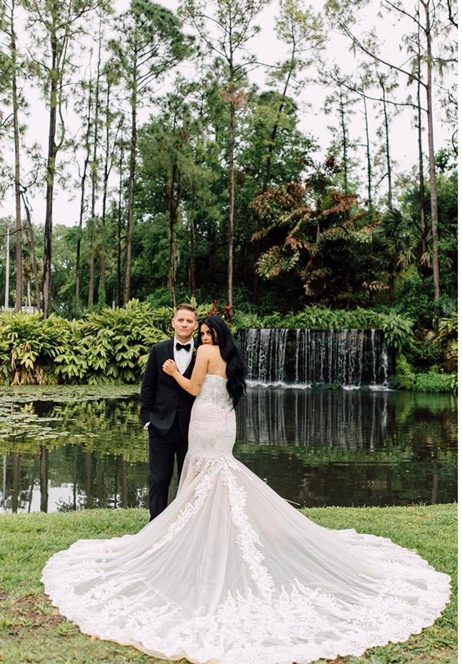 Gorgeous back of wedding dress in front of central florida waterfall