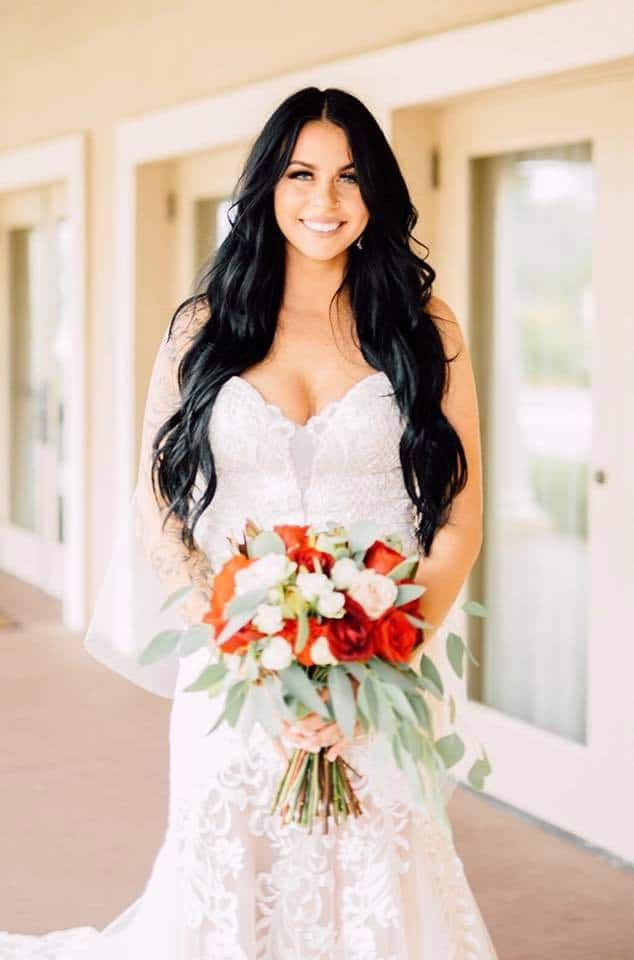 Bride with black hair in wedding dress holding bouquet