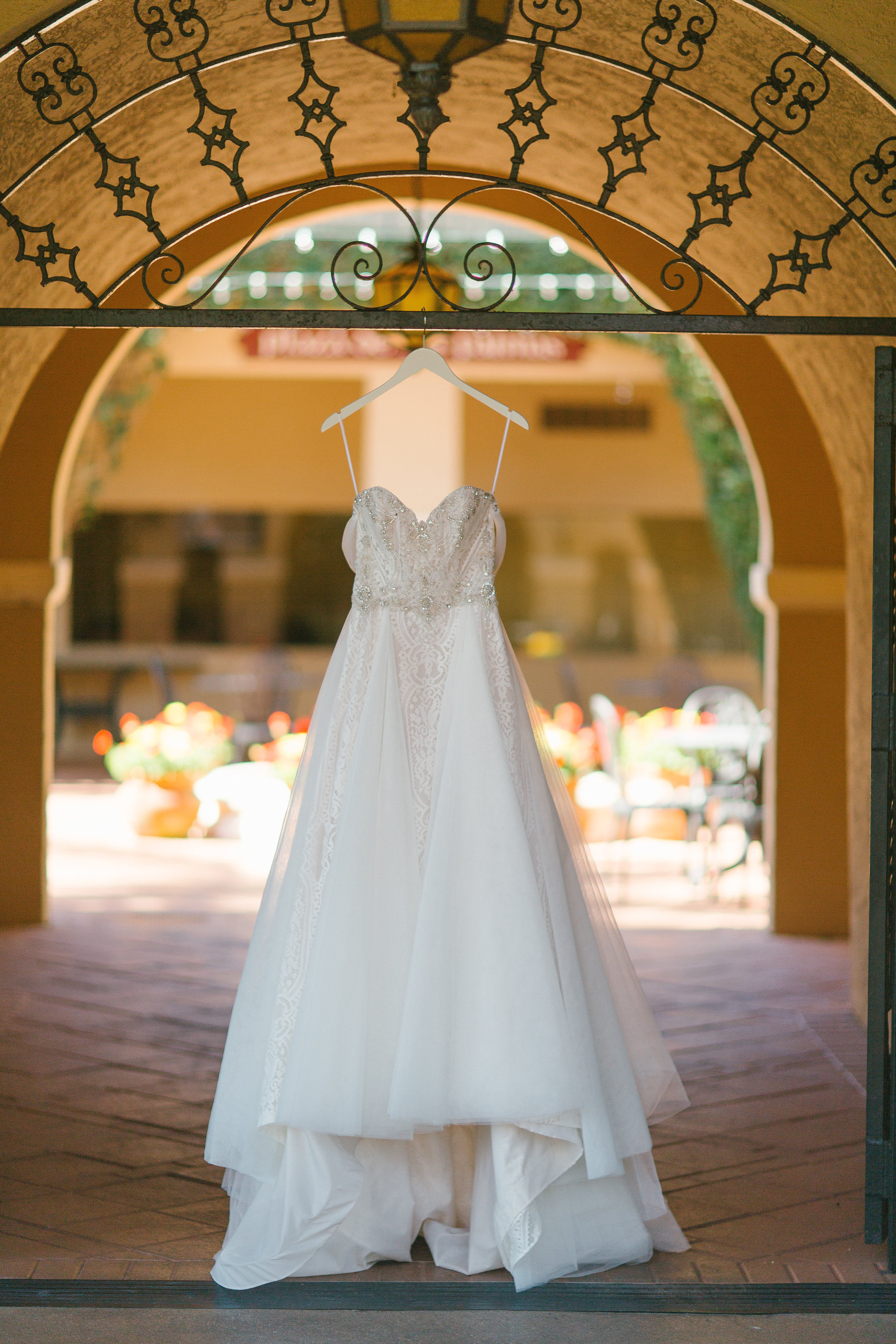 Wedding dress hanging from iron gate