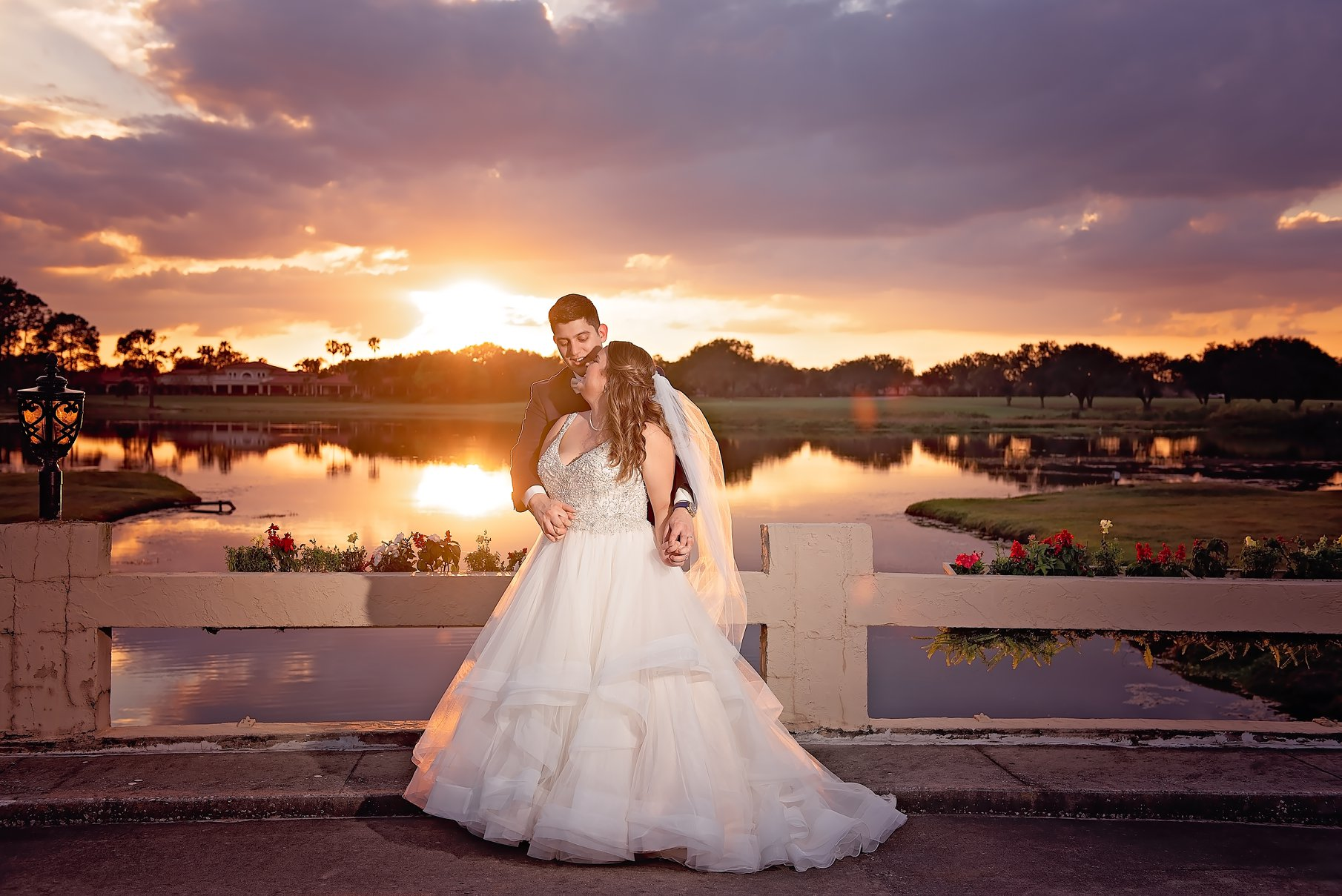 Gorgeous portrait of bride and groom on sunset bridge at sunset