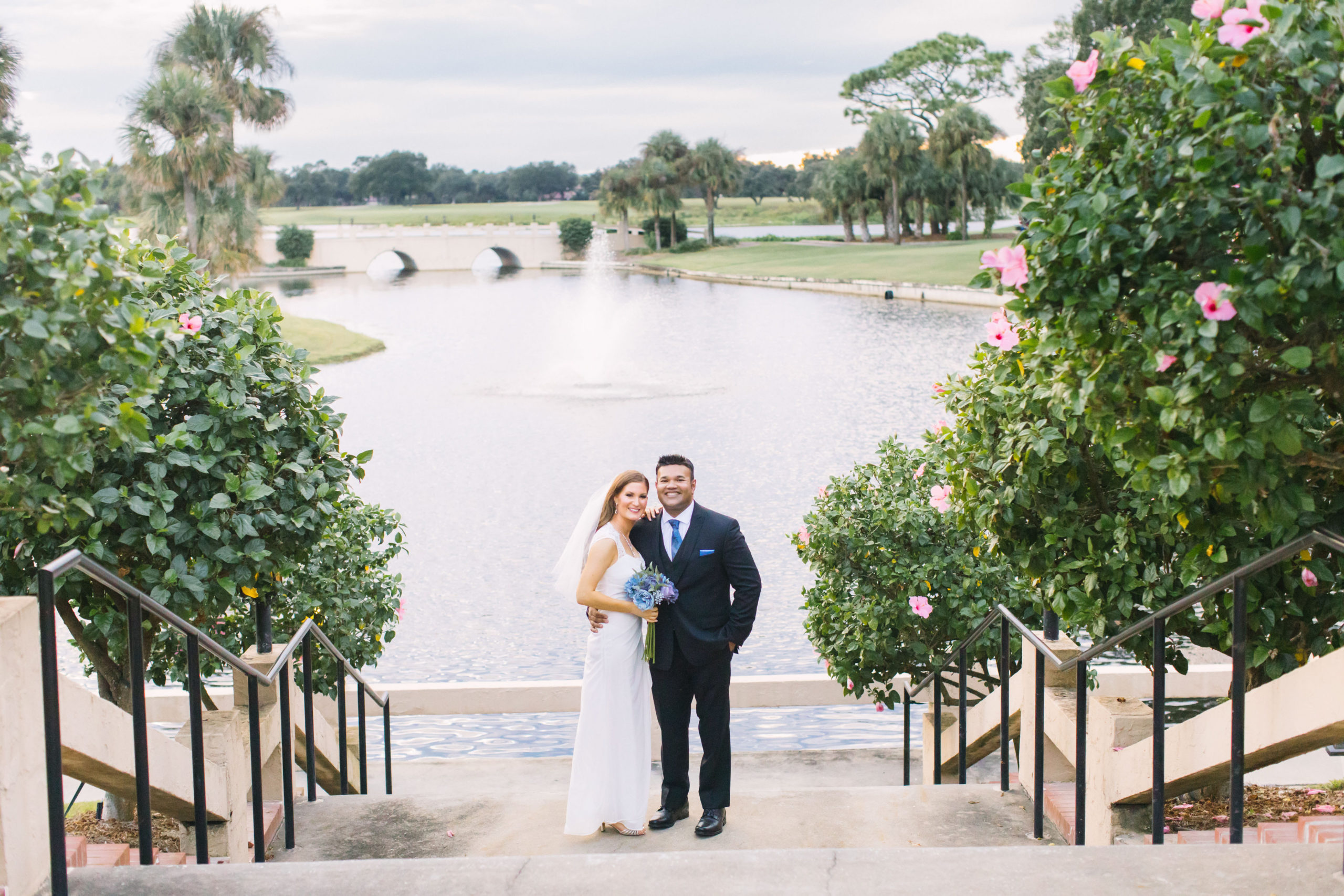 Bride with blue bouquet standing next to her groom on a staircase of pink hibiscus trees in front of a lake