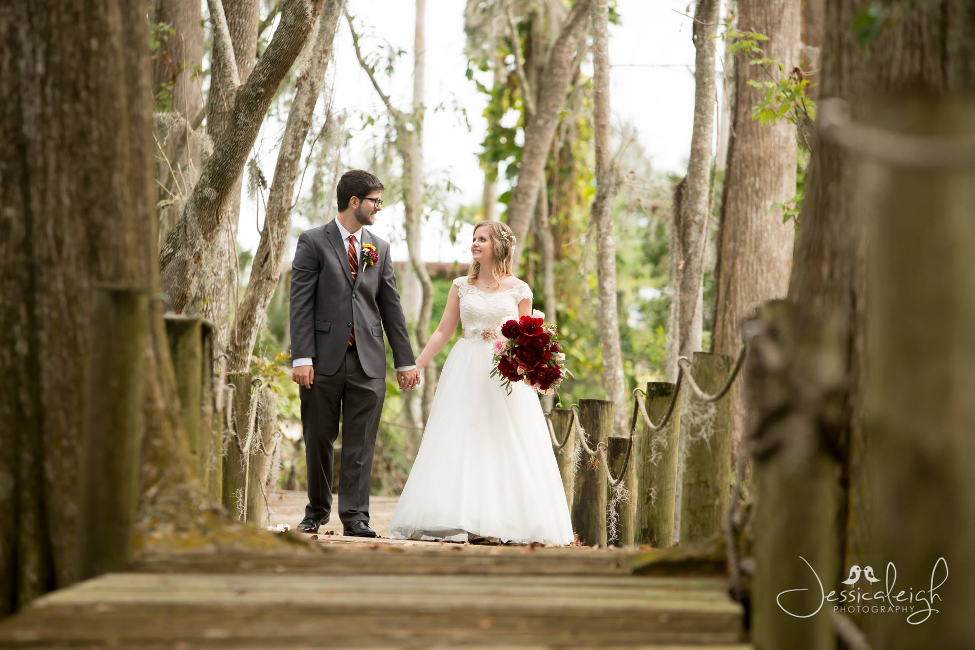 Bride carrying red flowers holding grooms hand while walking on a boardwalk