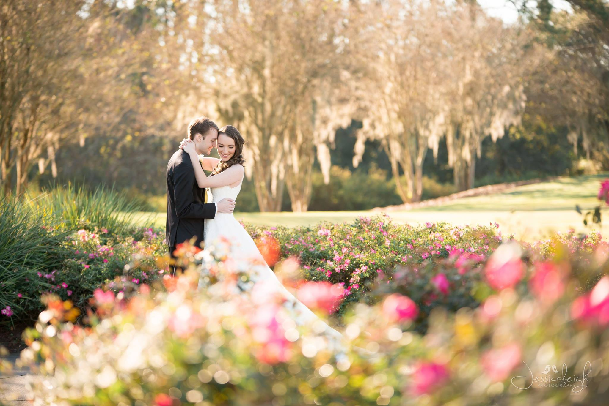Bride and Groom in front of oak tree behind beautiful pink flowers