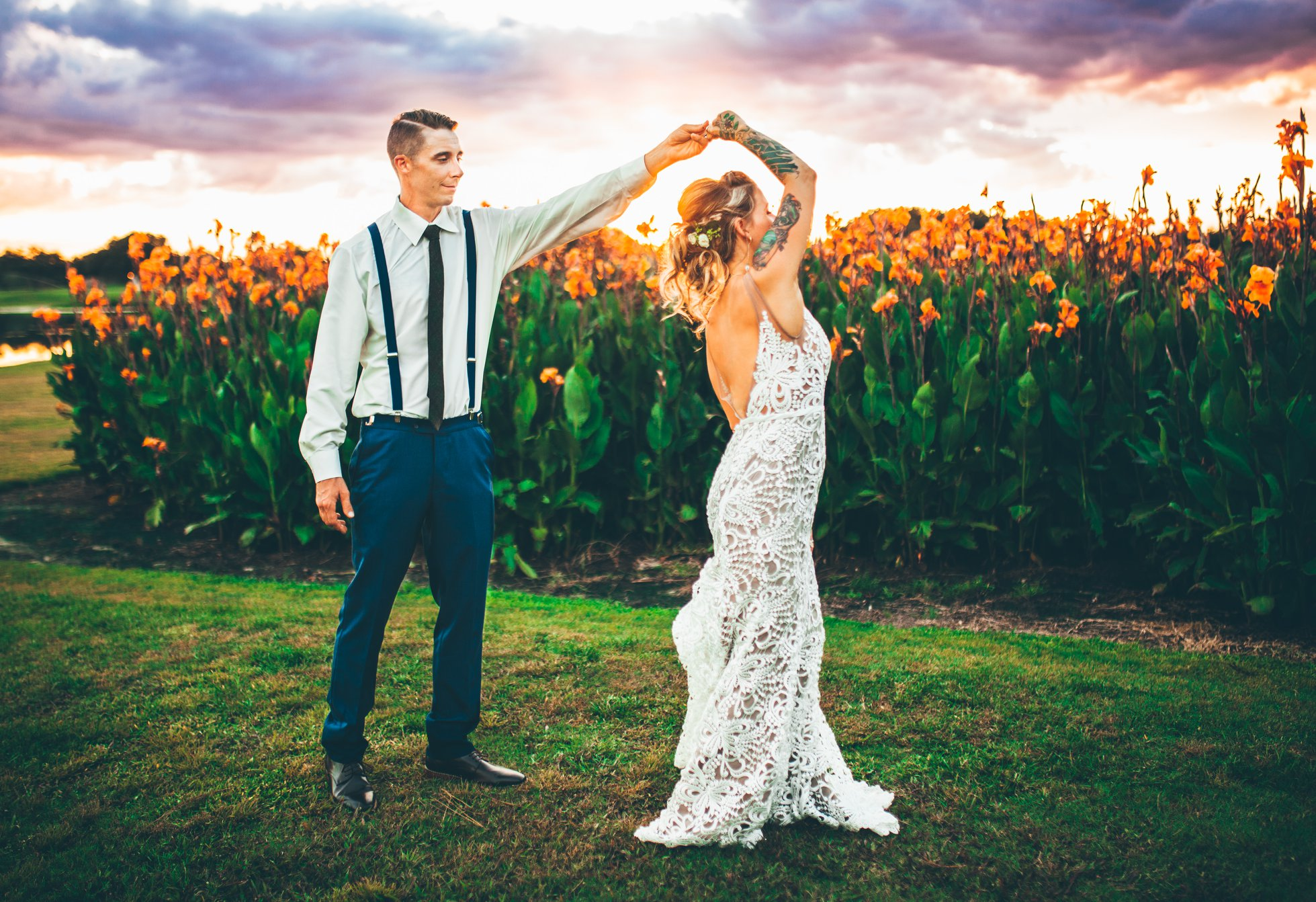 Bride and groom dancing in front of large orange lillies at sunset