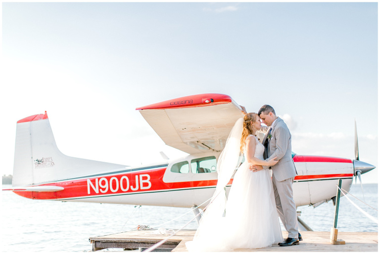 Bride and Groom standing on the docks in front of a seaplane getting ready to take off