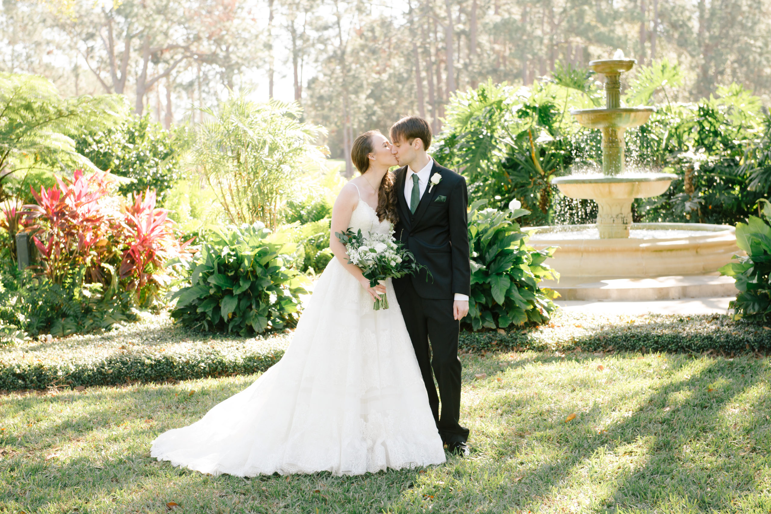 Picture of Bride holding flowers kissing groom in front of fountain
