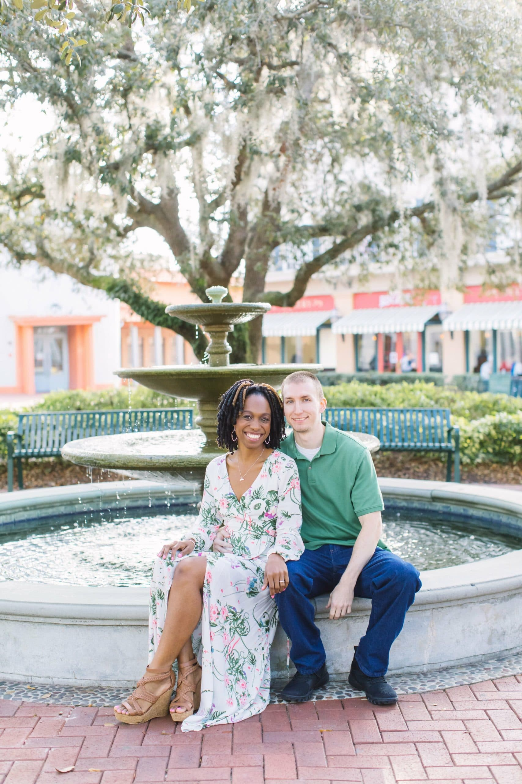 African American Female Bride with Caucasian Male Groom in Green Shirt sitting in front of park fountain