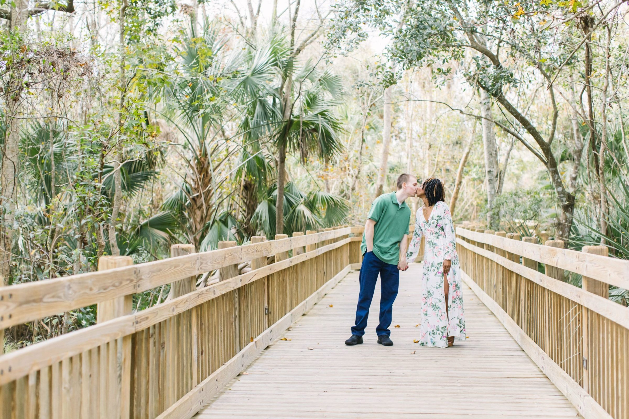 couple walking on park boardwalk through palm trees