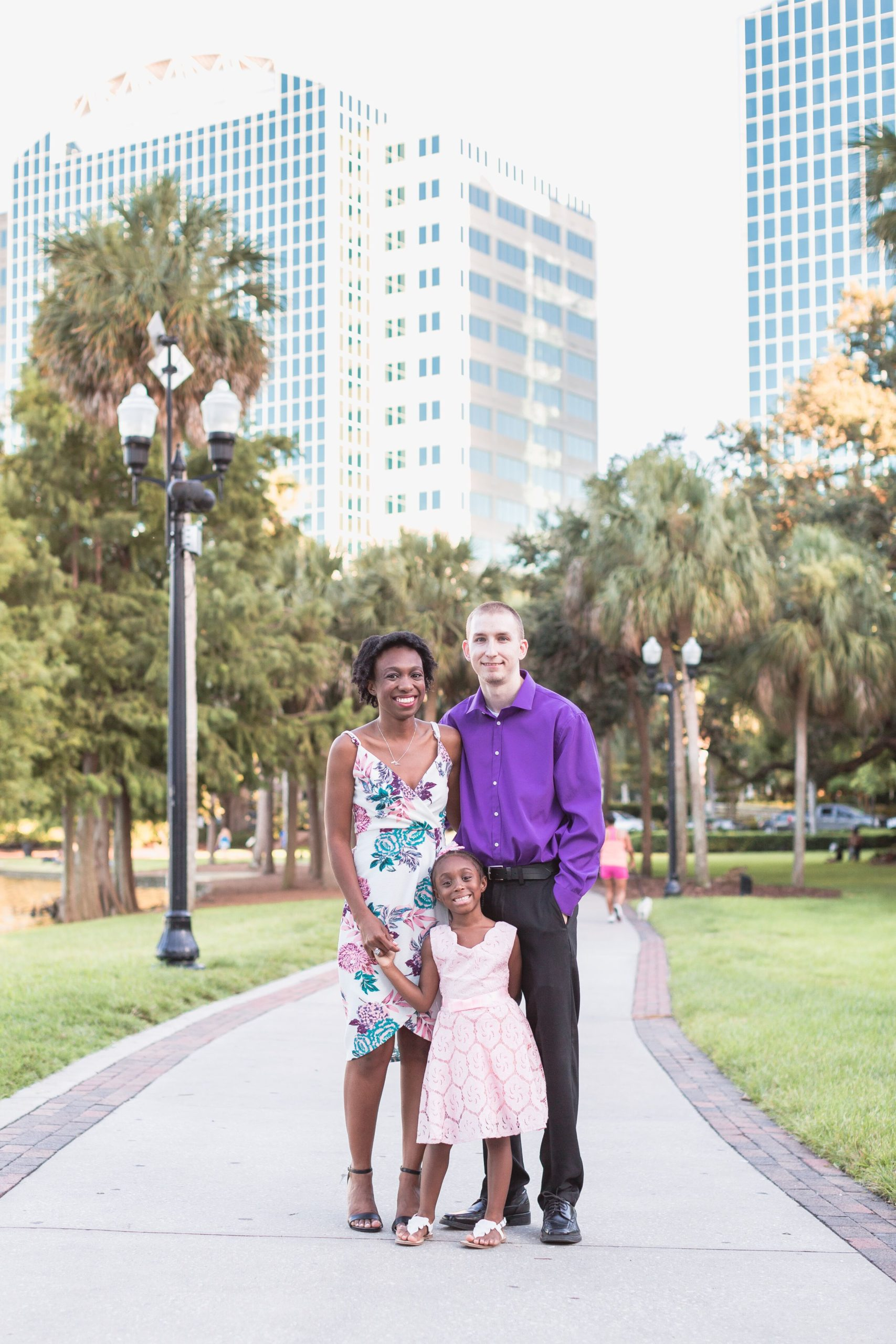 Man in purple shirt, woman in floral dress and child in pink dress taking family photo in a park